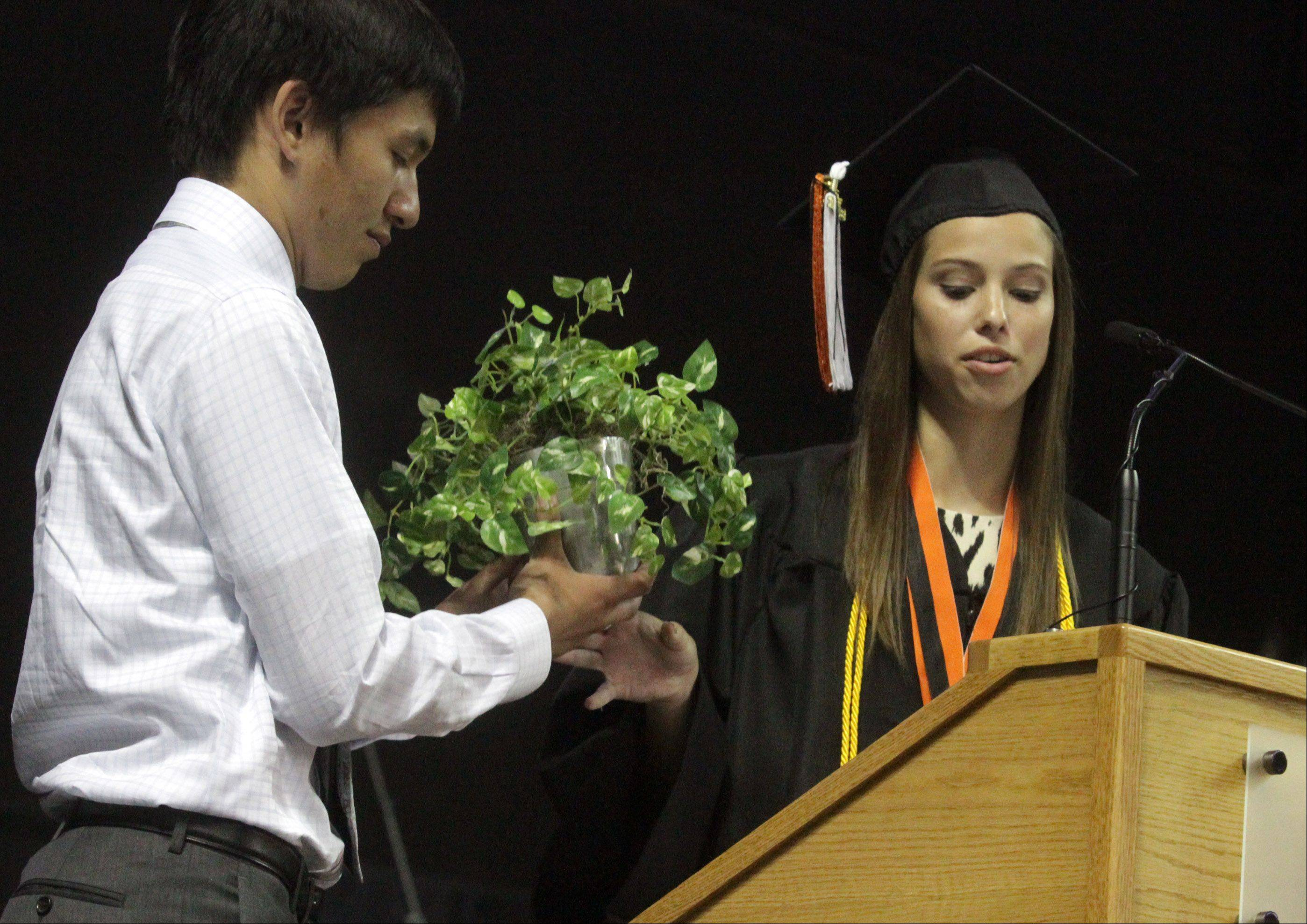 Libertyville High School 2013 student President Dana Humen presents the school's traditional ivy to 2014 student President Joseph Amdur.
