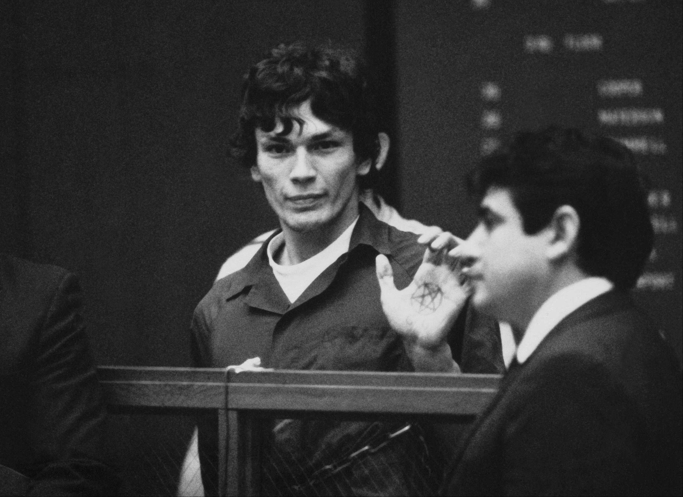 This 1985 file photo shows Richard Ramirez, center, know as the Night Stalker, shows a pentagram on the palm of his hand in court. California corrections officials say convicted serial killer Ramirez, known as the Night Stalker, has died in prison.
