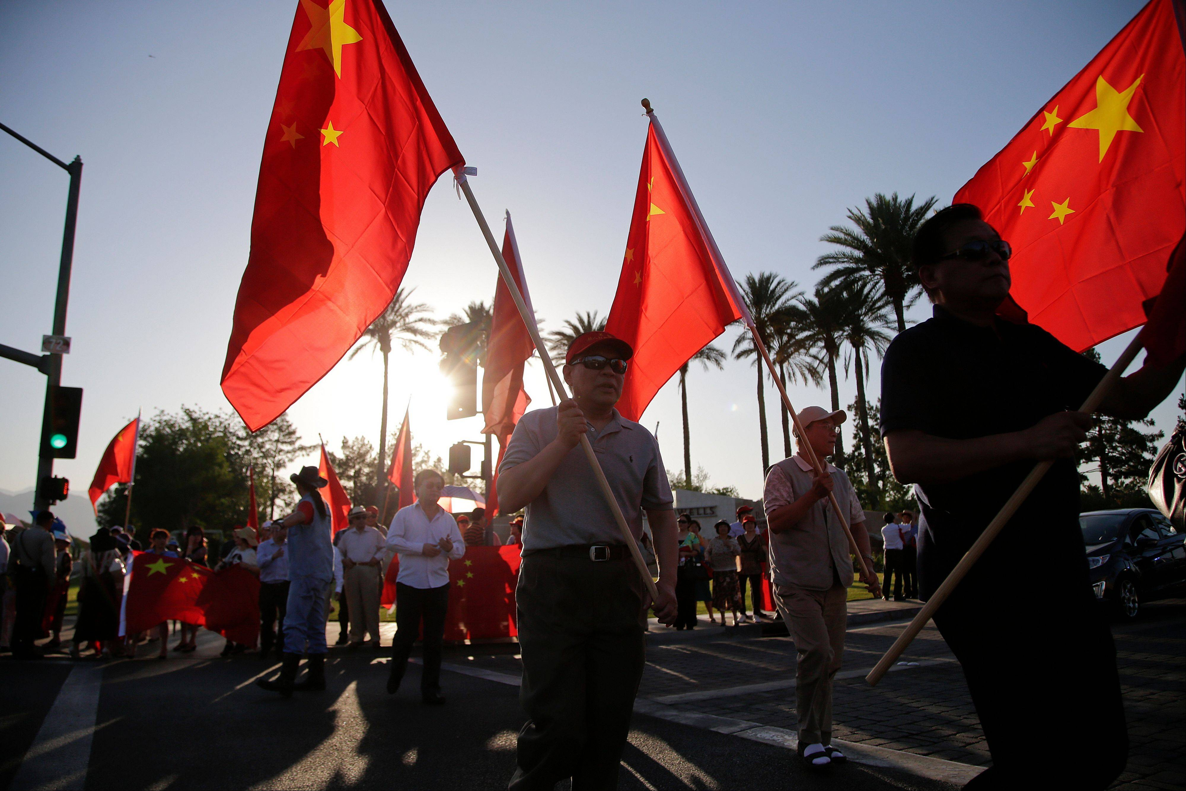 Supporters of Chinese President Xi Jinping carry Chinese flags Thursday as they wait for the arrival of President Xi in Indian Wells, Calif.