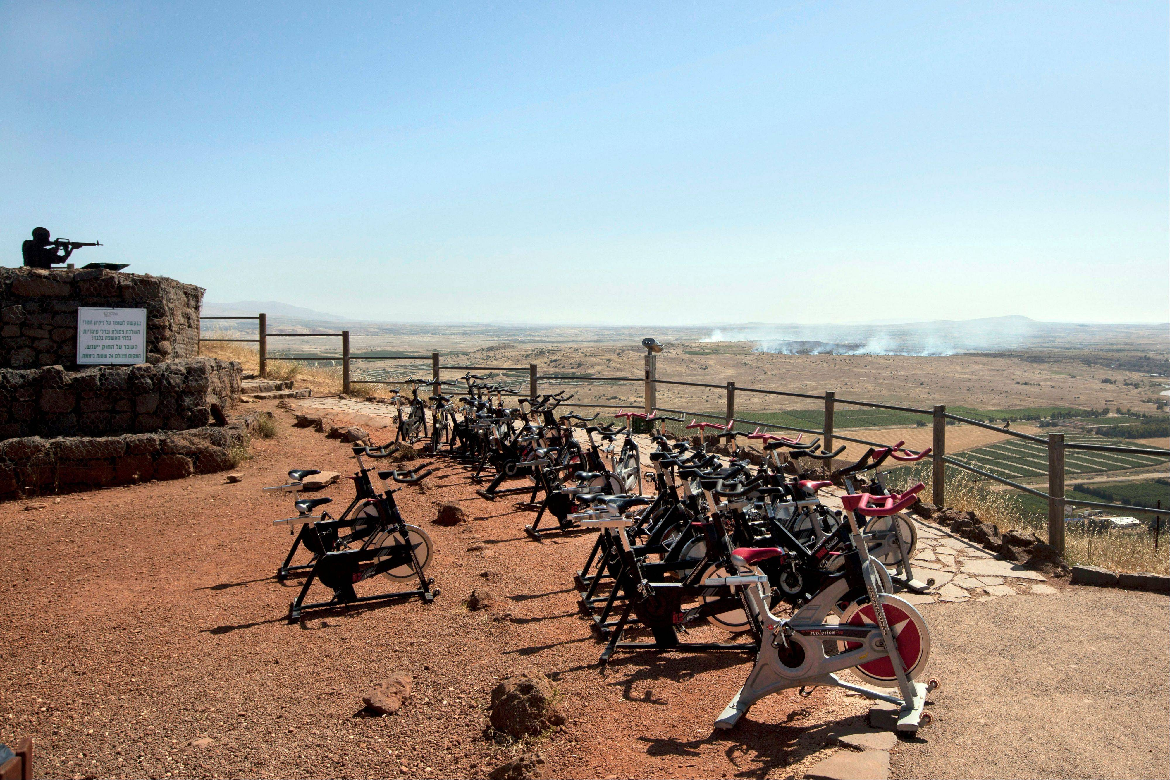 Exercise bicycles are seen Friday as smoke rises from fighting in Syria as seen from an observation point on Mt. Bental in the Golan Heights. Syrian rebels on Thursday briefly captured a crossing point along a cease-fire line with Israel in the contested Golan Heights.