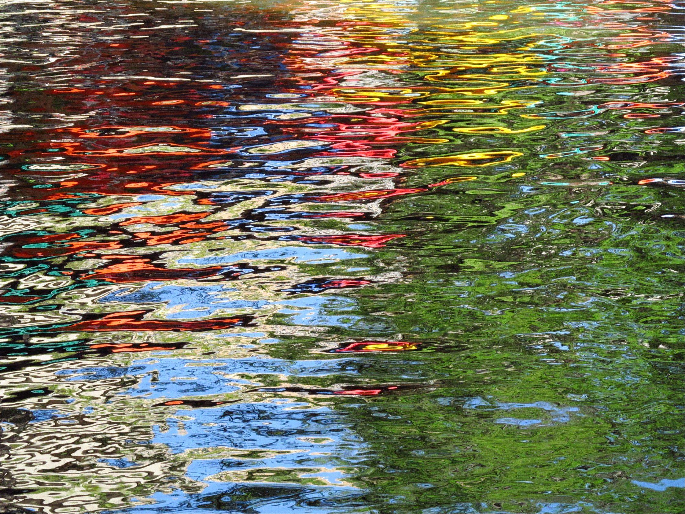 The colorful umbrellas of an outdoor cafe reflected in the water of the San Antonio River Walk in April 2013.