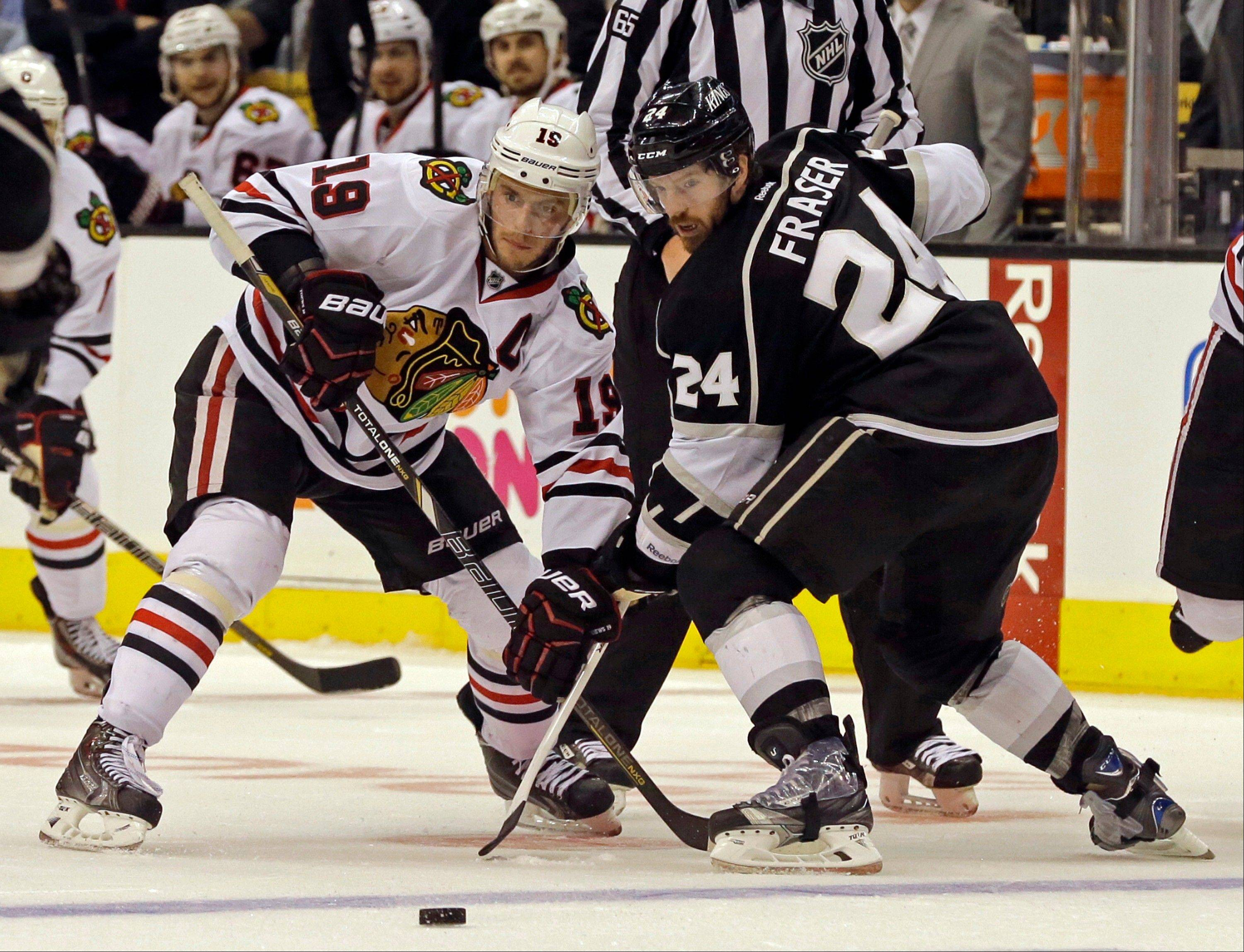 Los Angeles Kings center Colin Fraser (24) and Chicago Blackhawks center Jonathan Toews (19) maneuver in the third period of Game 4 of the NHL hockey Stanley Cup Western Conference finals in Los Angeles Thursday, June 6, 2013. The Blackhawks won, 3-2.