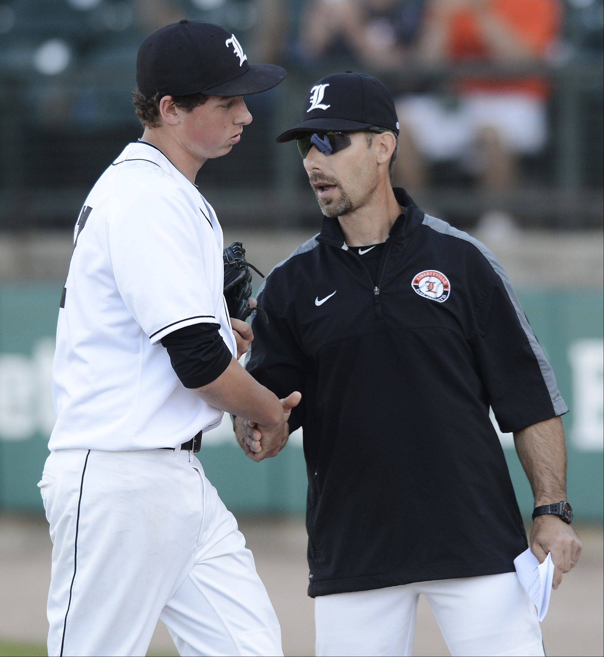 Libertyville starting pitcher Jeff Burton gets a handshake from coach Jim Schurr as he comes out of the game during the Class 4A state baseball semifinal against St. Charles East at Silver Cross Field in Joliet Friday.