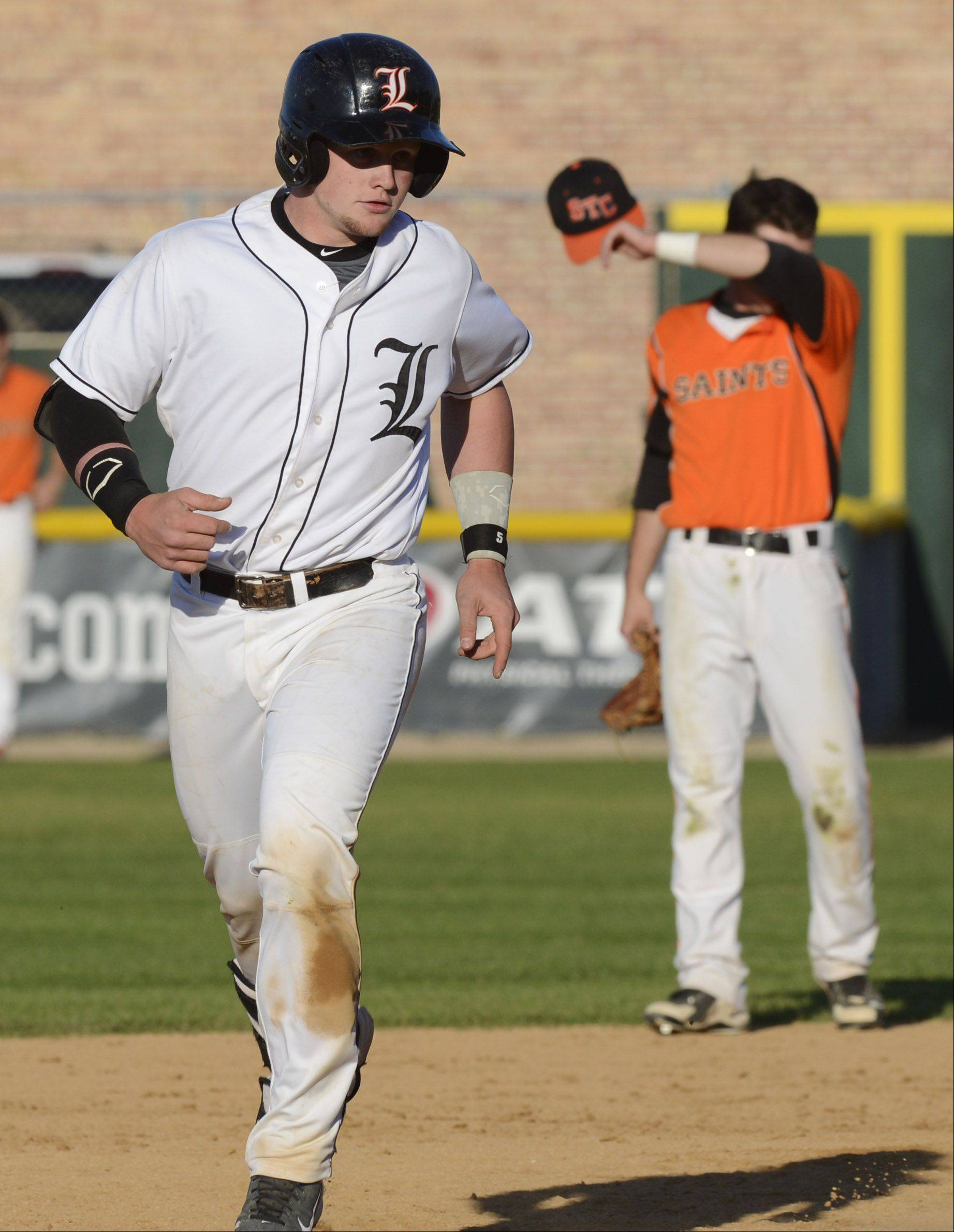 Libertyville's Evan Skoug rounds the bases after hitting a fourth-inning grand slam against St. Charles East during the Class 4A state baseball semifinals at Silver Cross Field in Joliet Friday.