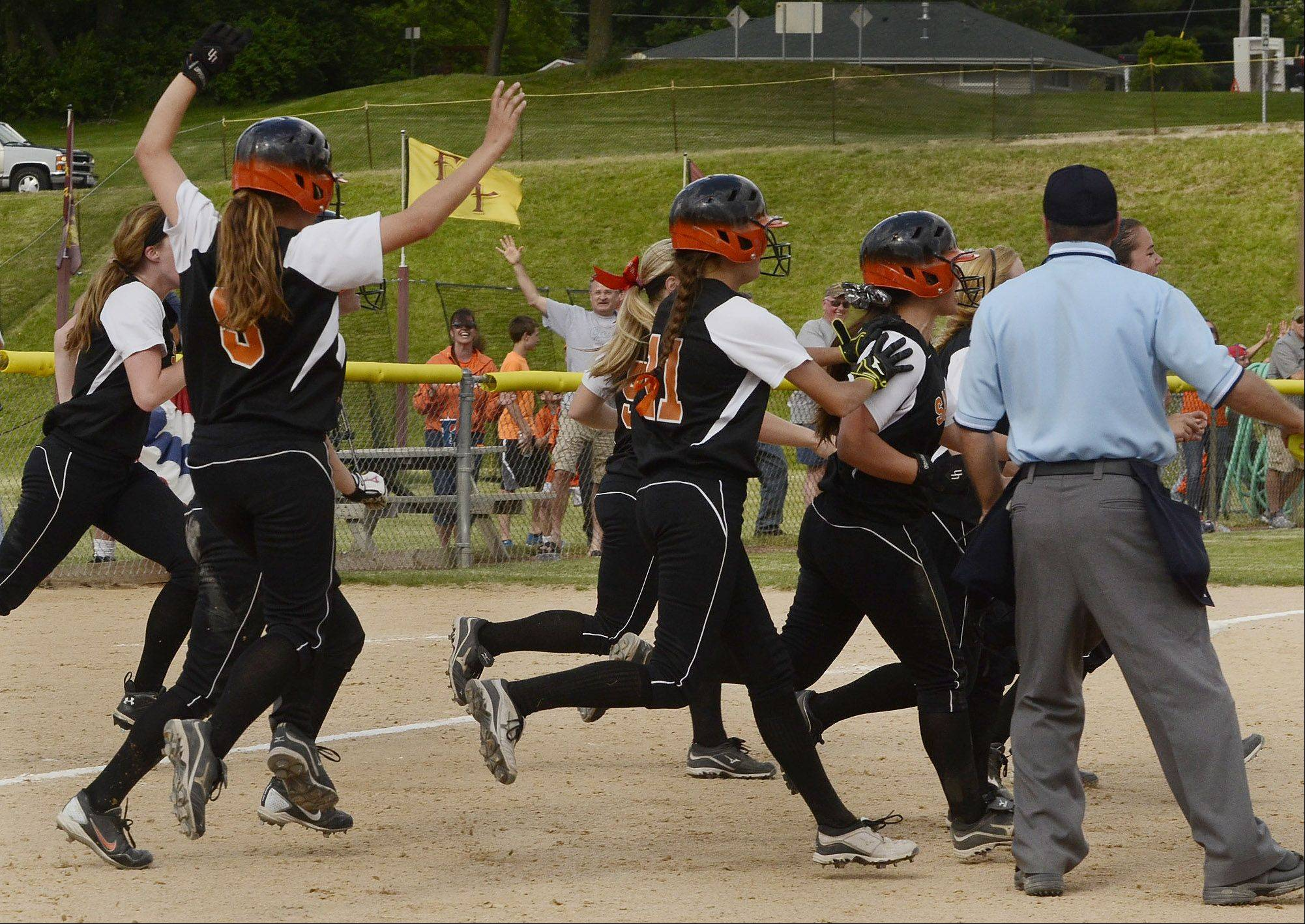 St. Charles East players pour out of the dugout after winning in the bottom of the seventh inning on a 2-run double by Olivia Lorenzini in the Class 4A state semifinals.
