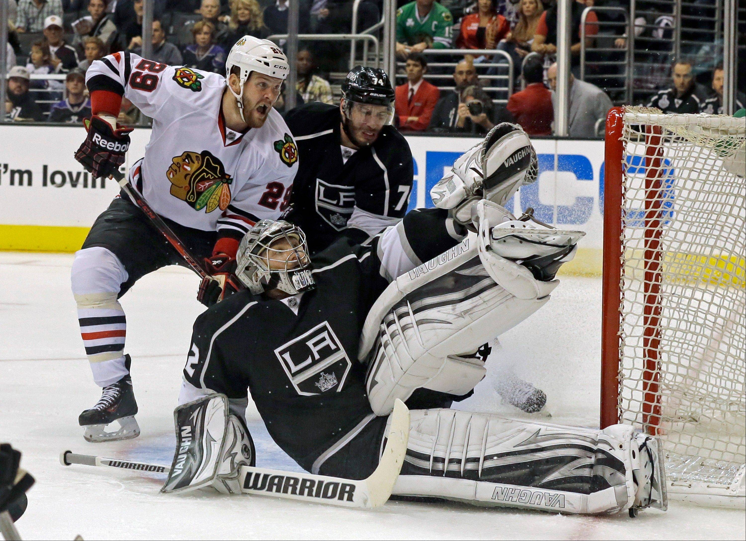 Kings goalie Jonathan Quick saves a shot on goal in front of center Dwight King (74) and Chicago Blackhawks left winger Bryan Bickell (29) in the third period of Game 4 of the NHL hockey Stanley Cup playoffs Western Conference finals, in Los Angeles on Thursday, June 6, 2013.