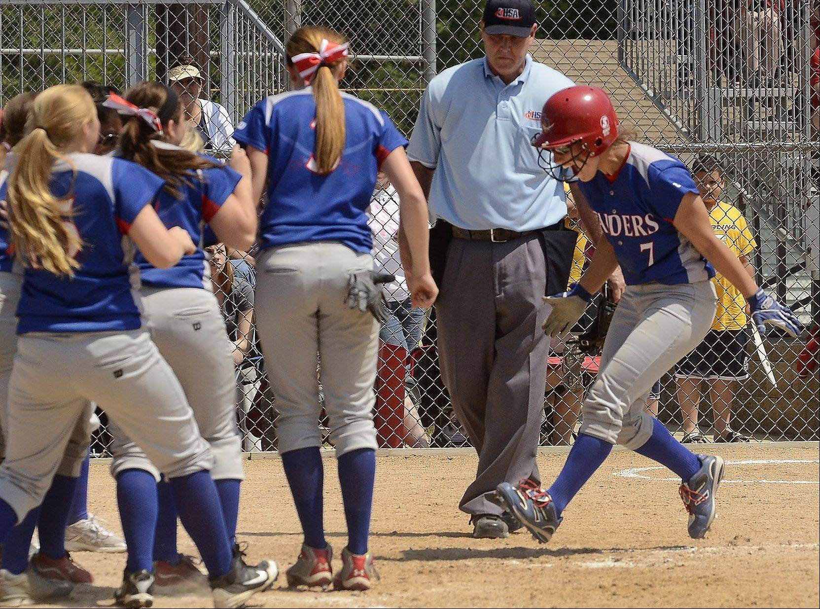Glenbard South's Hannah Taylor is met at home plate by her teammates after hitting a two-run home run in the 4th inning of the Class 3A state semifinal between Glenbard South and Tinley Park.