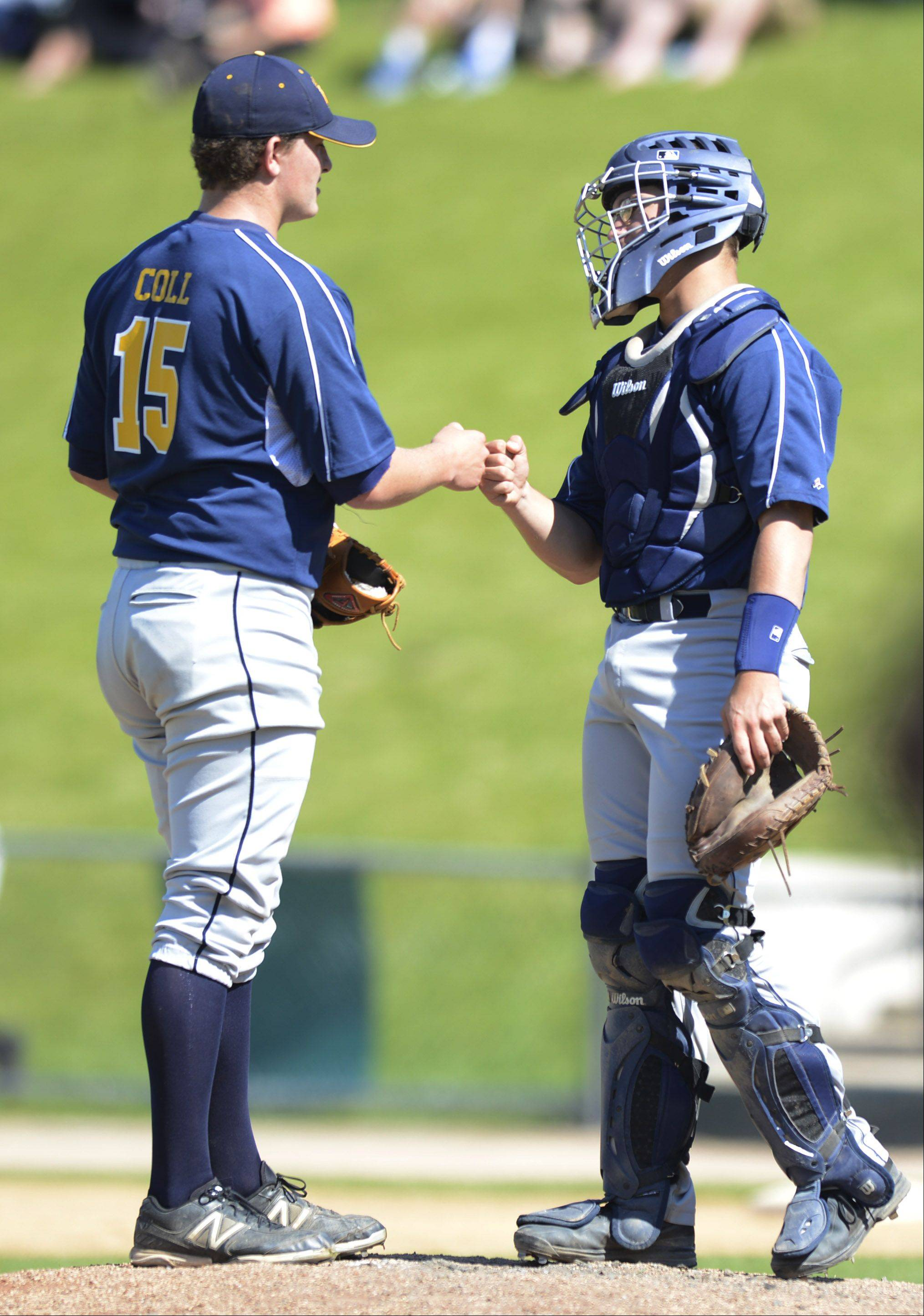 Neuqua Valley pitcher Cody Coll gets a fist bump from catcher Alex Wolanski during the Class 4A state baseball semifinals against Mt. Careml at Silver Cross Field in Joliet Friday.