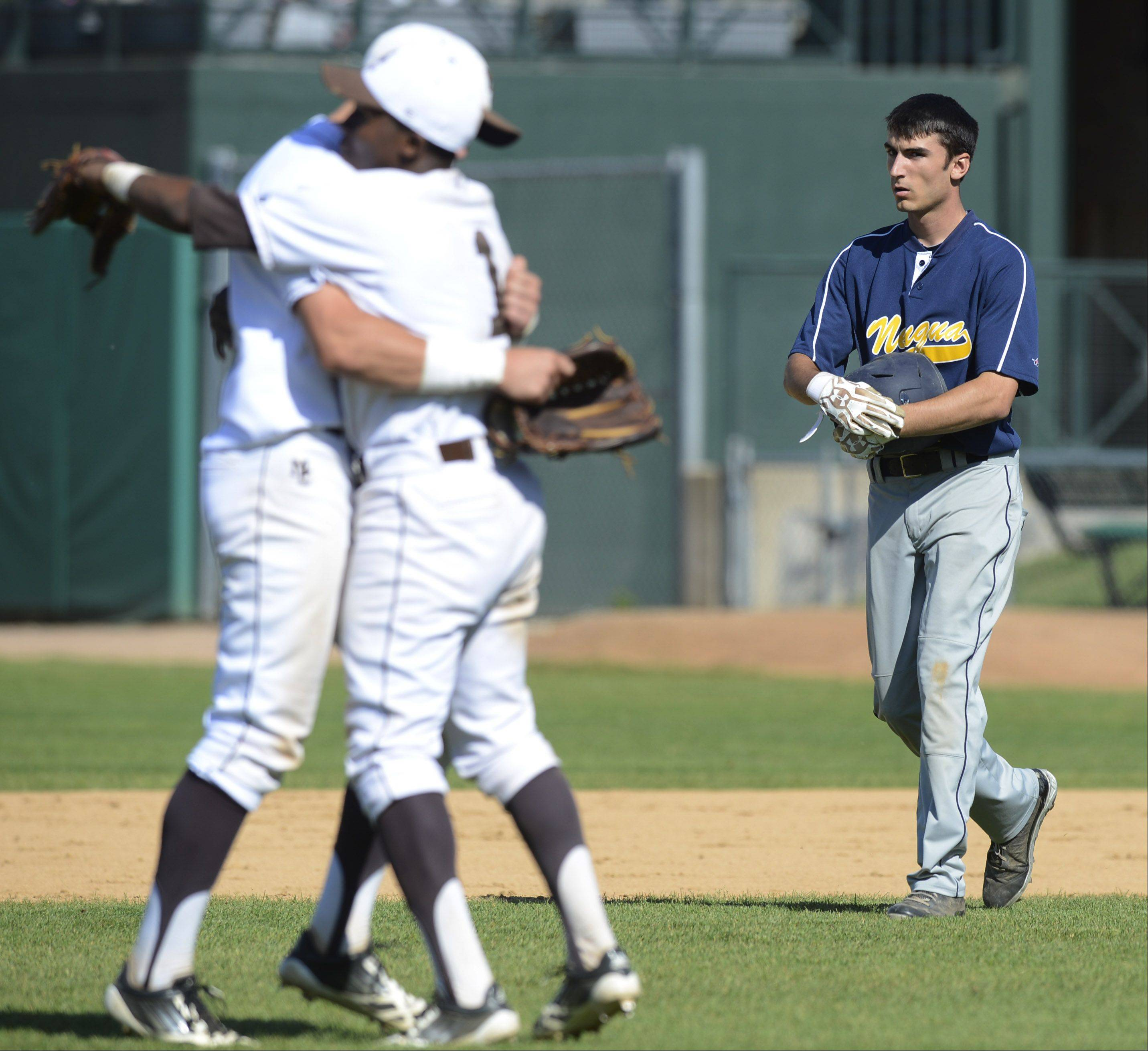 Neuqua Valley's Josh Piotrowski walks past celebrating Mt. Carmel players during the Class 4A state baseball semifinals at Silver Cross Field in Joliet Friday.