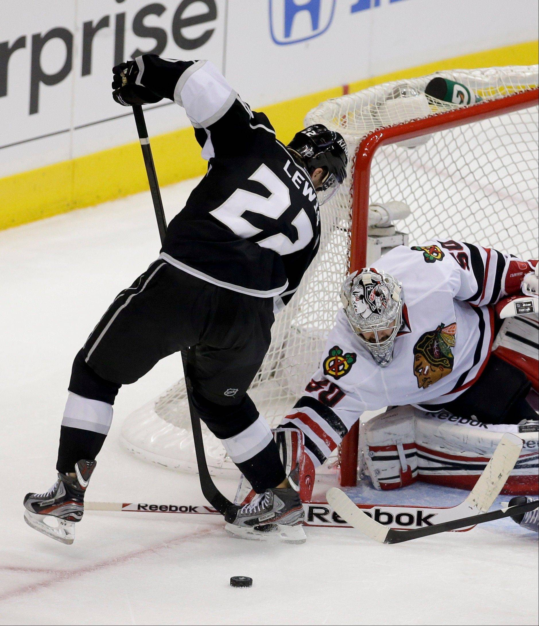 Chicago Blackhawks goalie Corey Crawford, right, blocks a shot by Los Angeles Kings center Trevor Lewis during the third period in Game 4 of the NHL hockey Stanley Cup playoffs Western Conference finals, in Los Angeles on Thursday, June 6, 2013. the Chicago Blackhawks won 3-2.