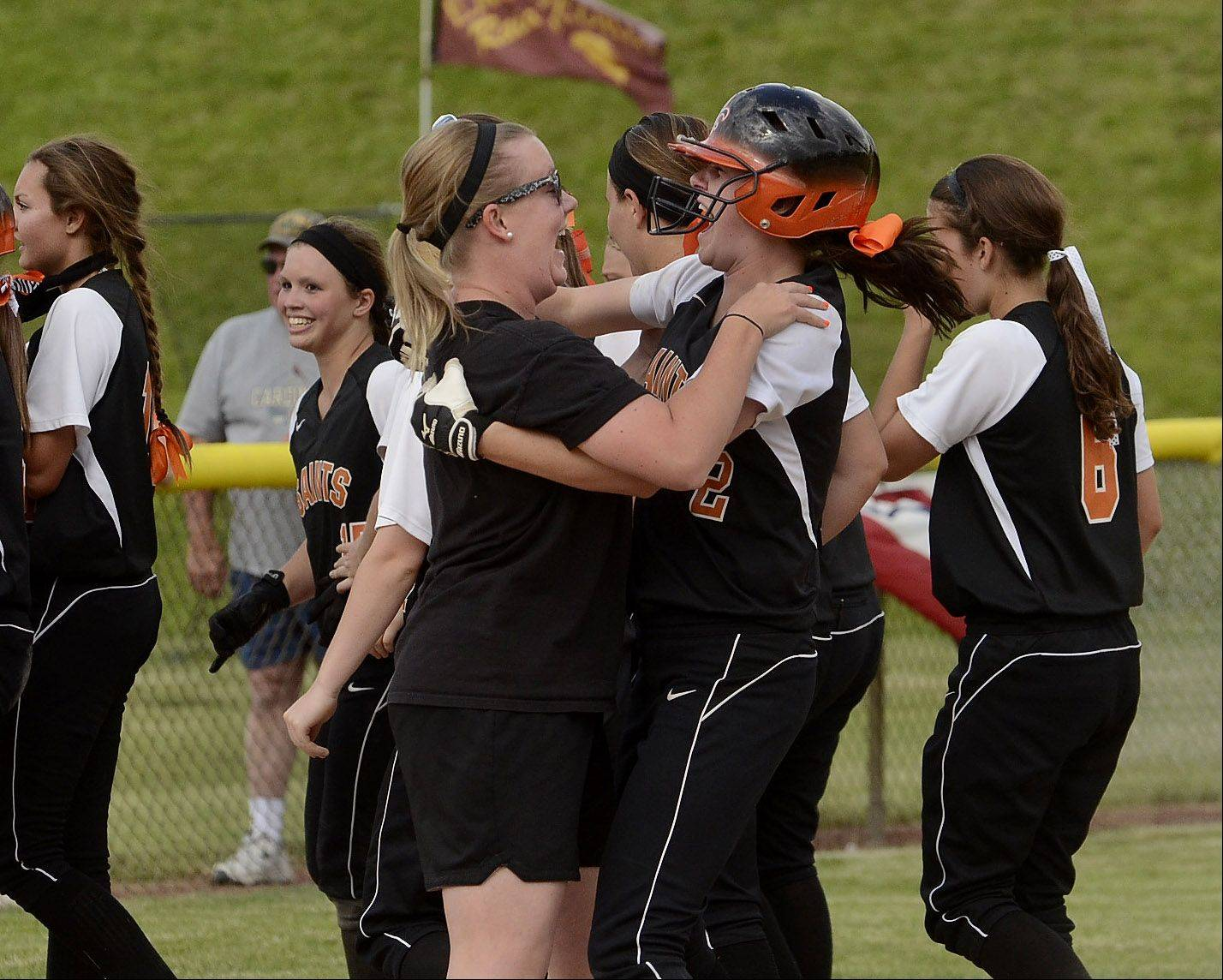 St. Charles East assistant coach Sarah Seward, left, embraces Olivia Lorenzini, after her two-run game winning double in the bottom of the 7th inning.