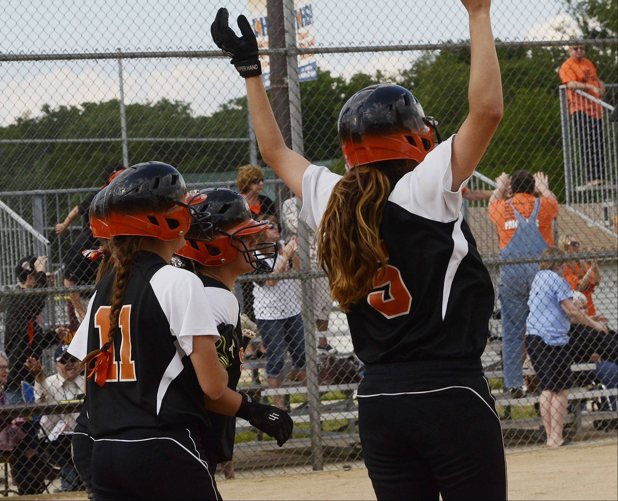 Tess Hupe, left and Lexi Perez of St. Charles East jump for joy at home plate after scoring the winning runs in the bottom of the 7th inning.
