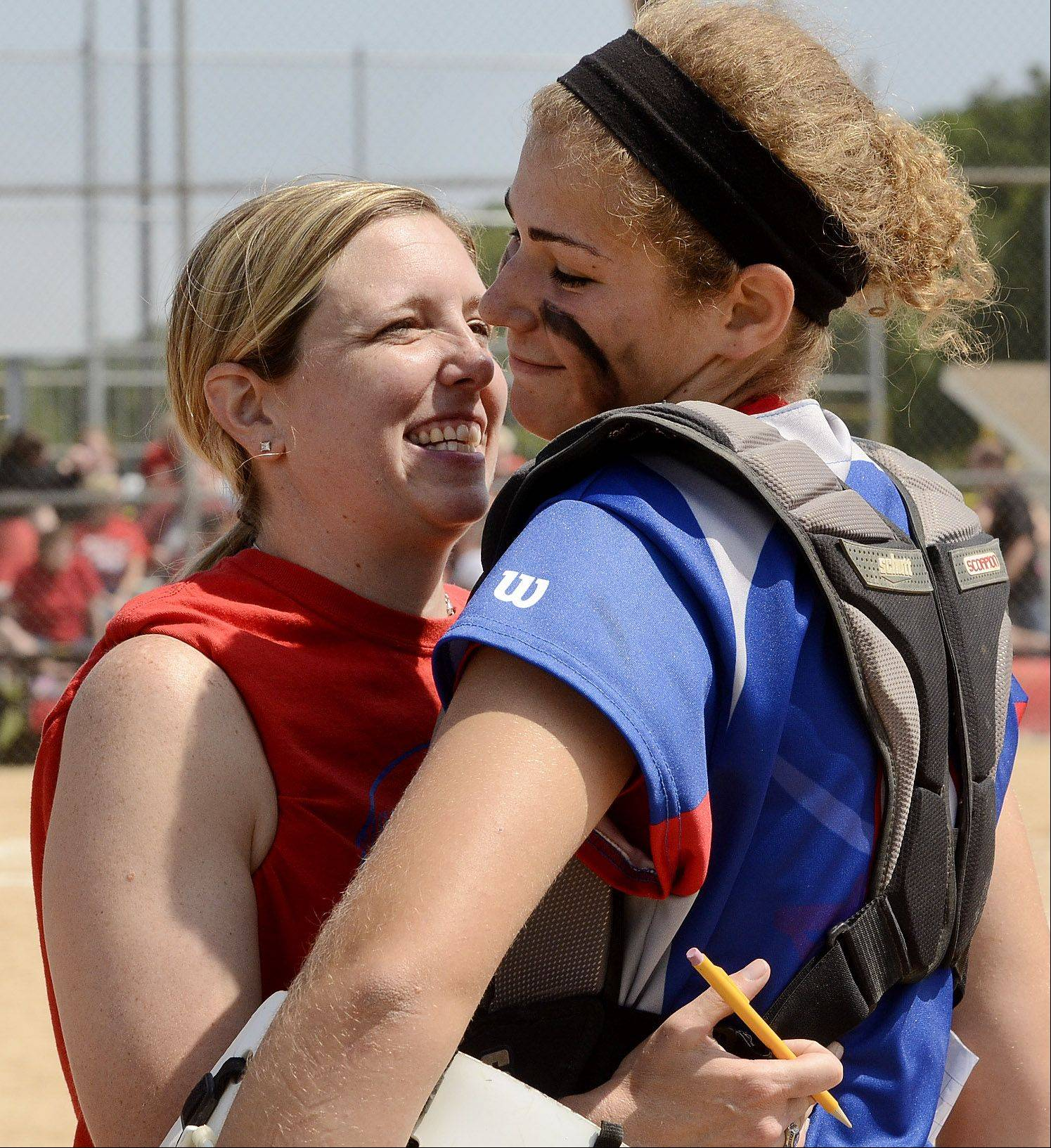 Glenbard South's head coach Julie Fonda hugs catcher Jane Trzaska after winning their Class 3A state semifinal game against Tinley Park.