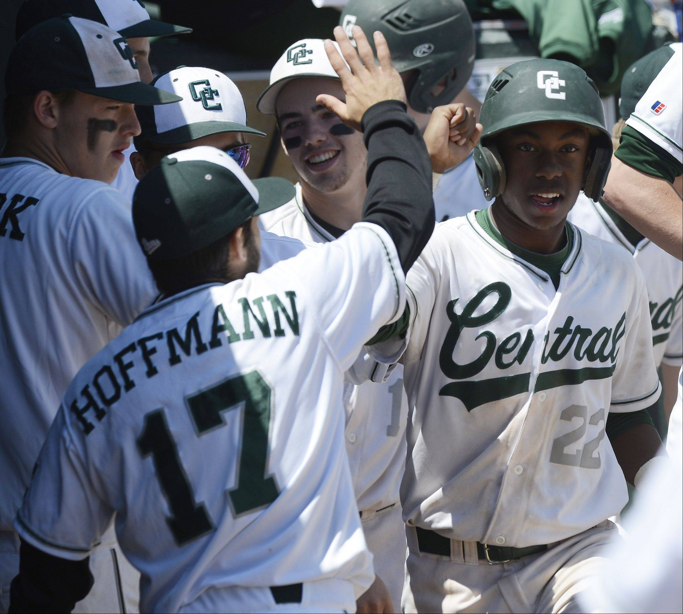 Grayslake Central's Sterling Dixon is greeted by teammates in the dugout after scoring in the sixth inning during the Class 3A state baseball semifinal against St. Francis at Silver Cross Field in Joliet Friday.