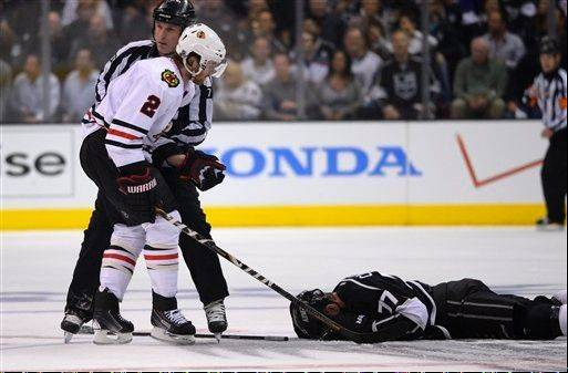 Los Angeles Kings center Jeff Carter, right, lays on the ice after being hit in the face with the stick of Chicago Blackhawks defenseman Duncan Keith during the second period in Game 3 of the NHL hockey Stanley Cup Western Conference finals, Tuesday, June 4, 2013, in Los Angeles.