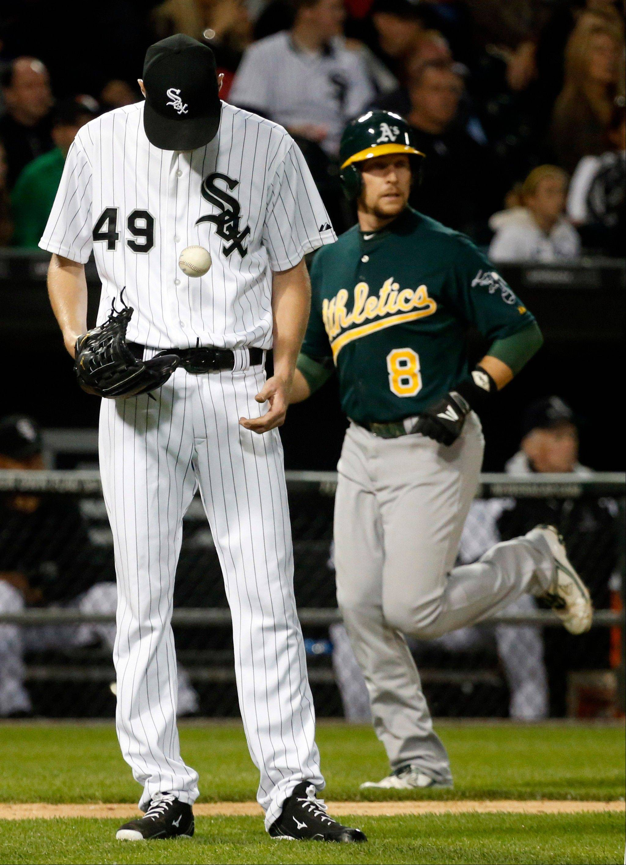 White Sox starter Chris Sale reacts after giving up a grand slam to the Athletics' Josh Donaldson as Jed Lowrie rounds third during the sixth inning Friday at U.S. Cellular Field.