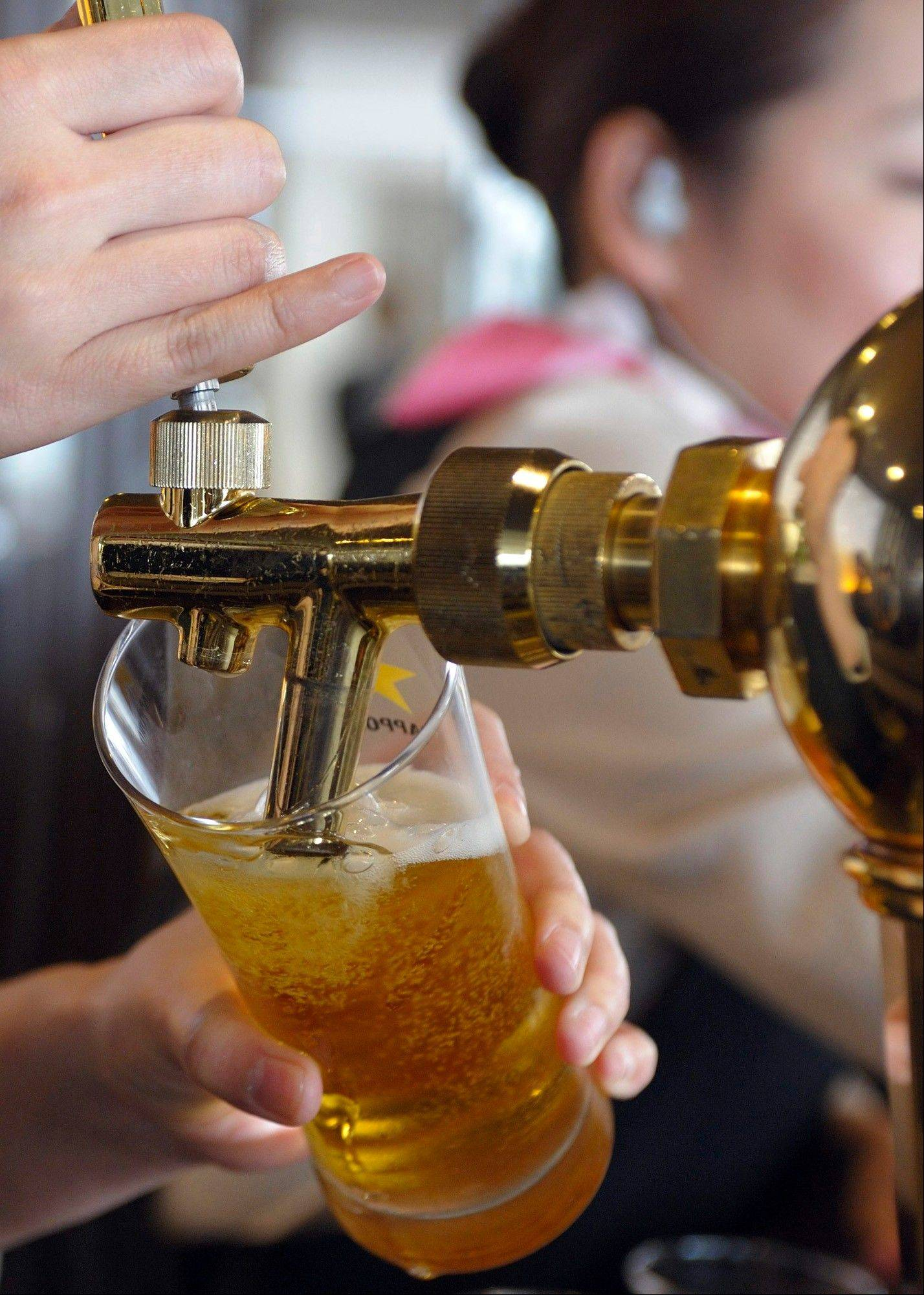 A Sapporo Breweries employee pours beer at the company�s plant in Chiba, Japan.