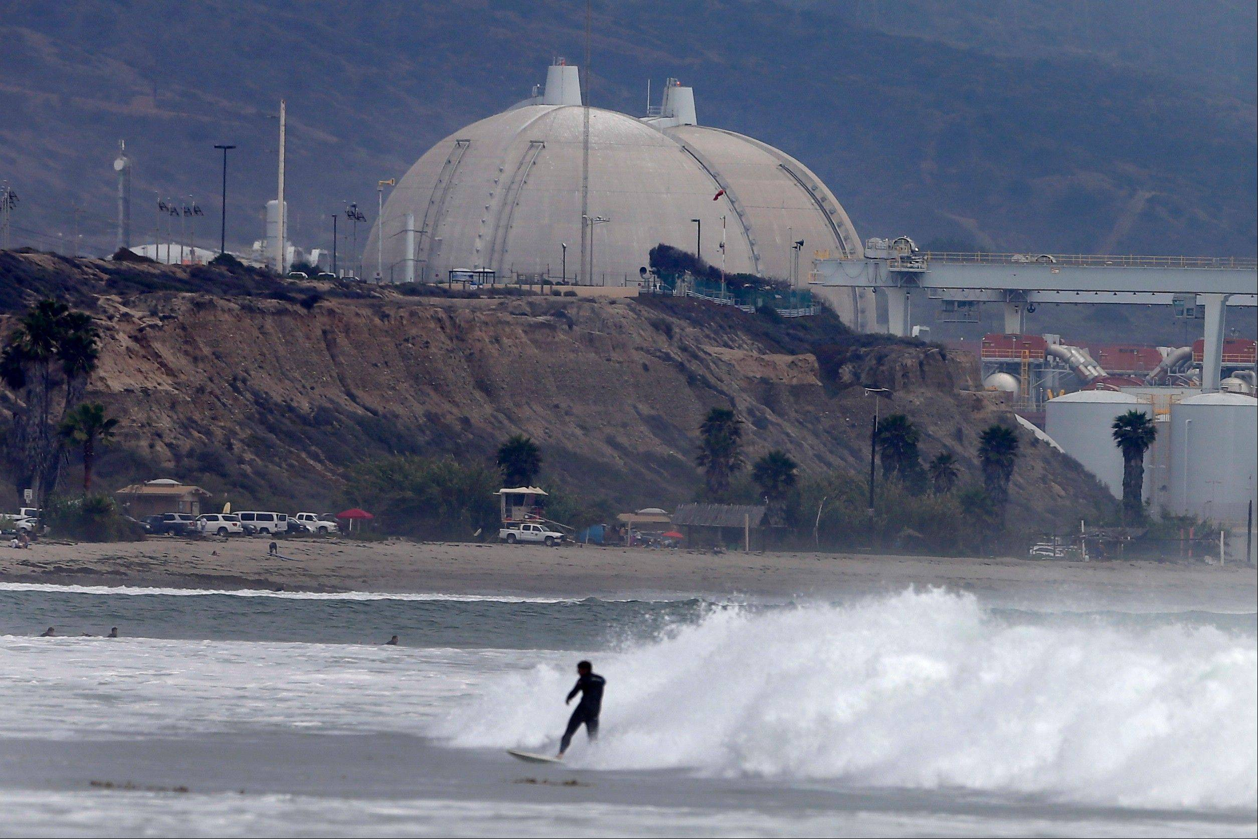 A surfer rides a wave Friday in front of the San Onofre nuclear power plant, in San Onofre, Calif.
