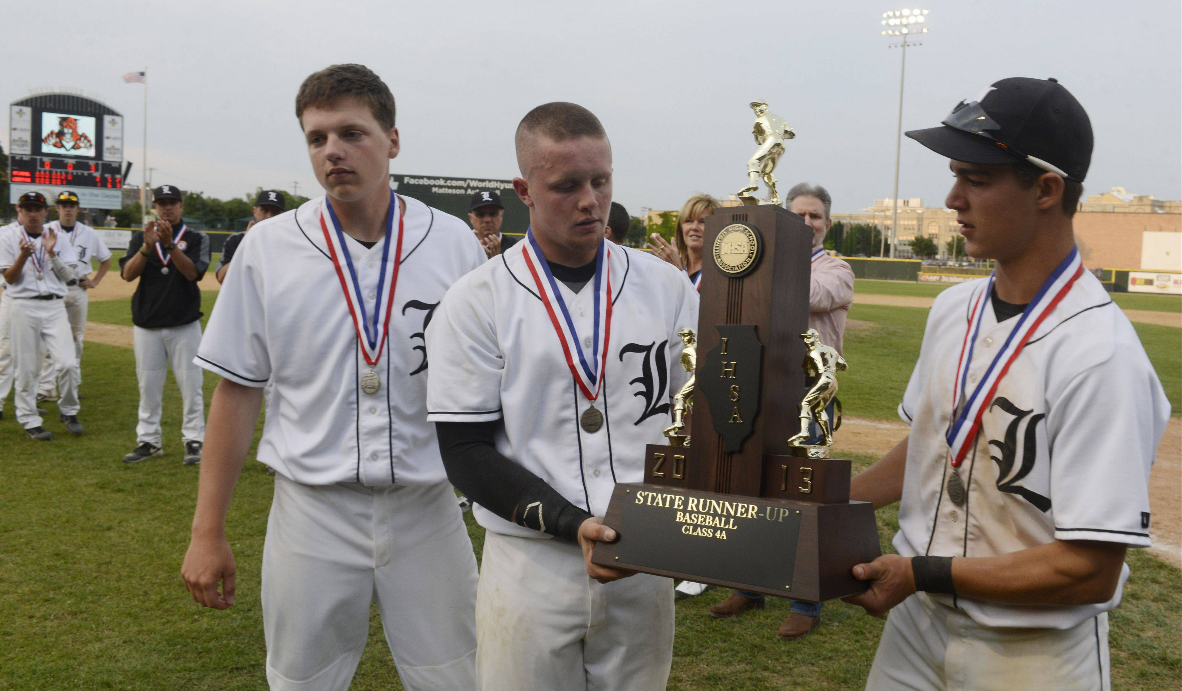 Left to right, Libertyville players Matt Vogt, Evan Skoug and Justin Guarnaccio hold the second-place trophy following the Wildcats� 2-1 loss to Mt. Carmel in the Class 4A state baseball championship game at Silver Cross Field in Joliet on Saturday.