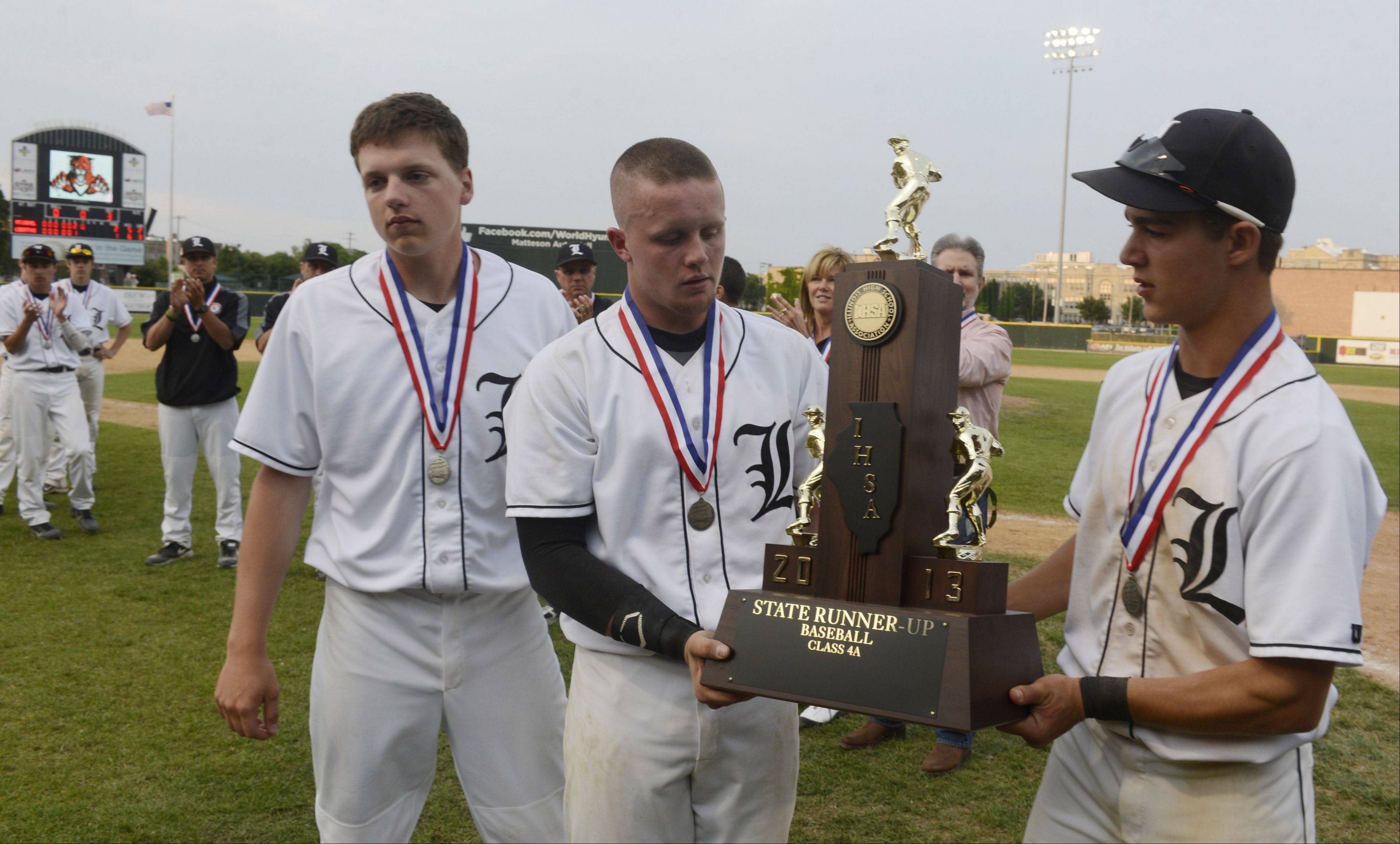 Libertyville players Matt Vogt, left, Evan Skoug, center, and Justin Guarnaccio hold the second-place trophy following their 2-1 loss to Mt. Carmel Saturday in the Class 4A state baseball championship game at Silver Cross Field in Joliet.
