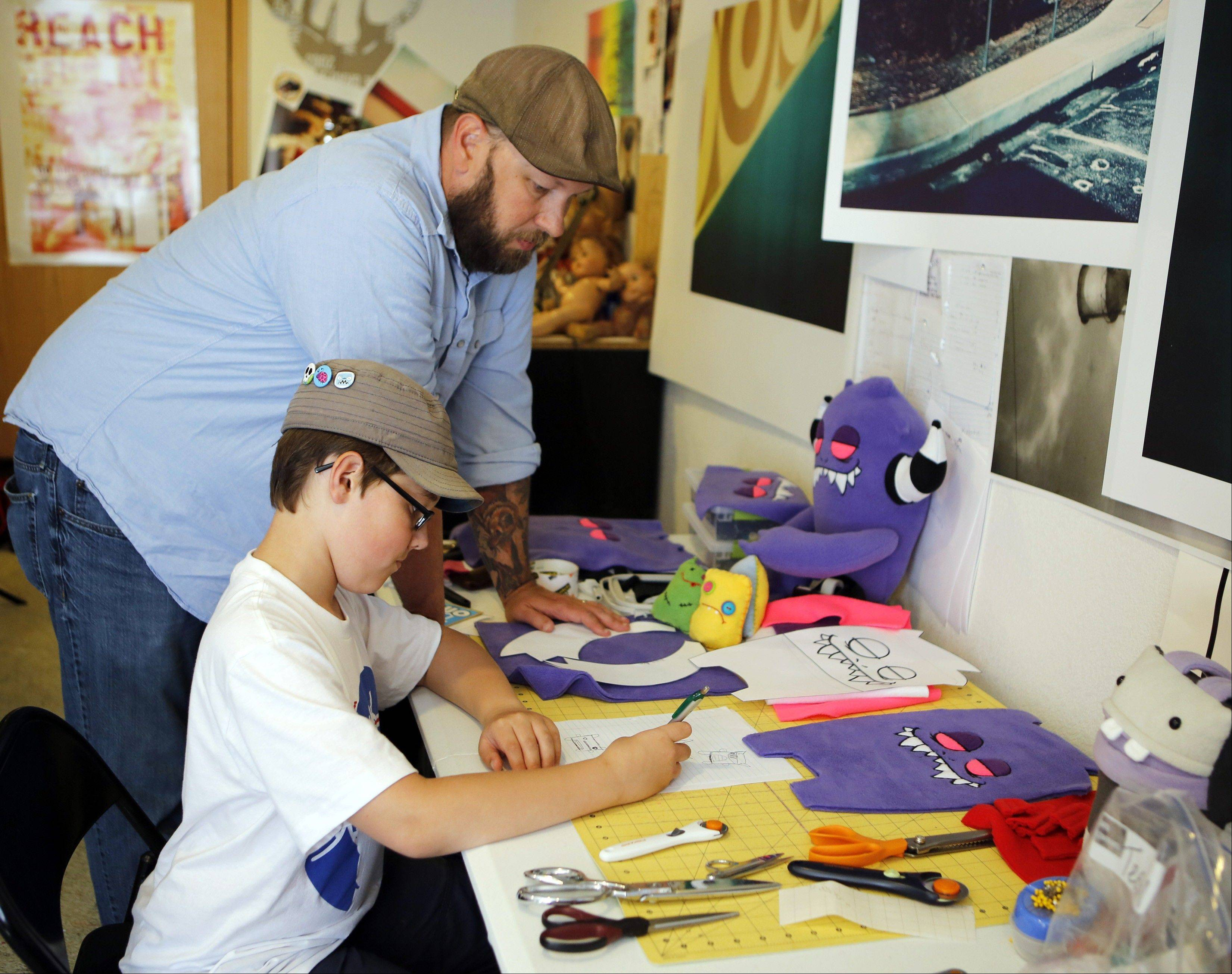 Ray Tollison looks over the shoulder of his son Sam as he works on a drawing of a monster doll at their home in Fort Collins, Colo. The Tollisons launched Monster to Love, a company that makes plush monster toys.