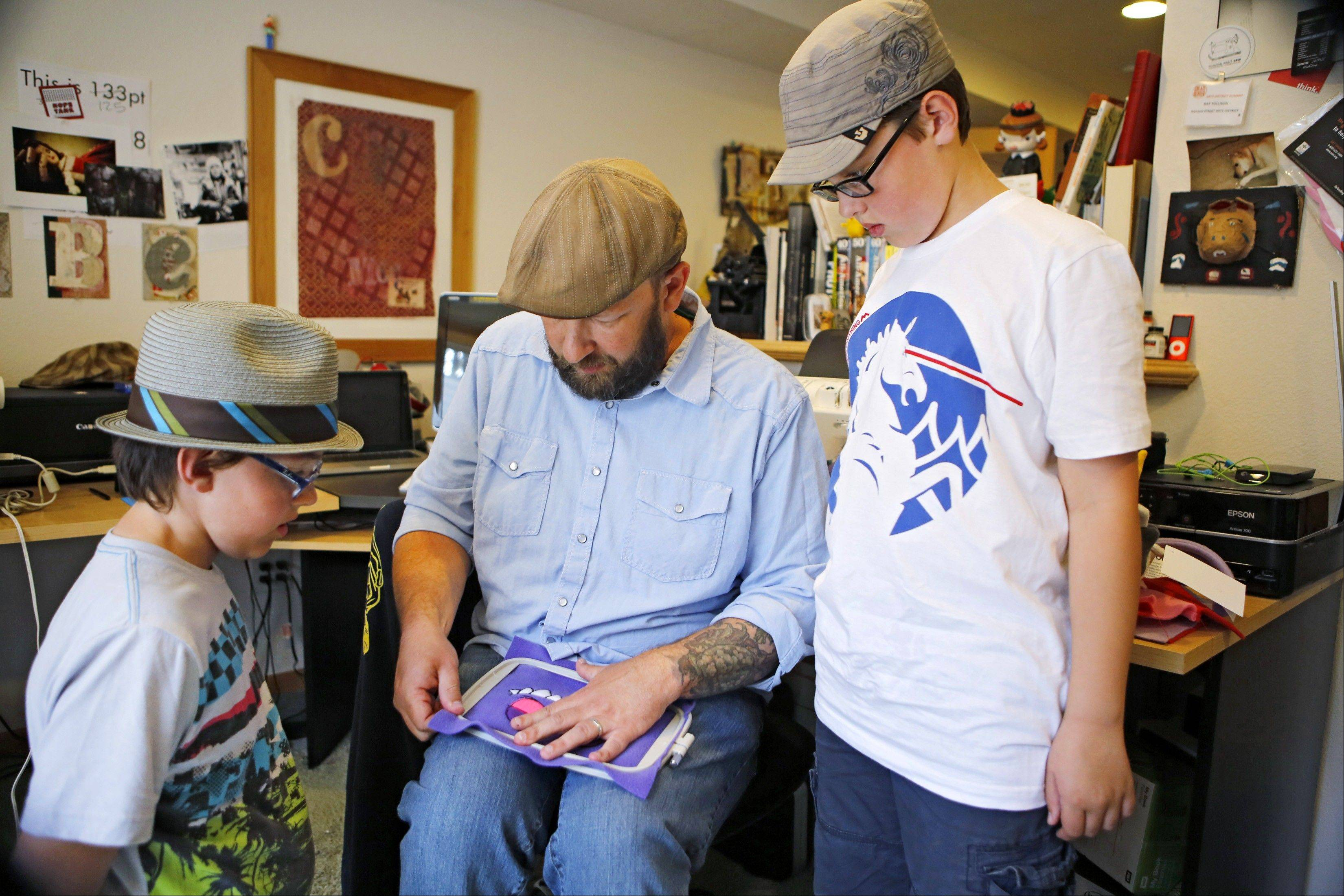 Ray Tollison inserts material into a frame for sewing, as sons Sam, left, and Ben look on at their home in Fort Collins, Colo. The Tollisons launched Monster to Love, a company that makes plush monster toys.