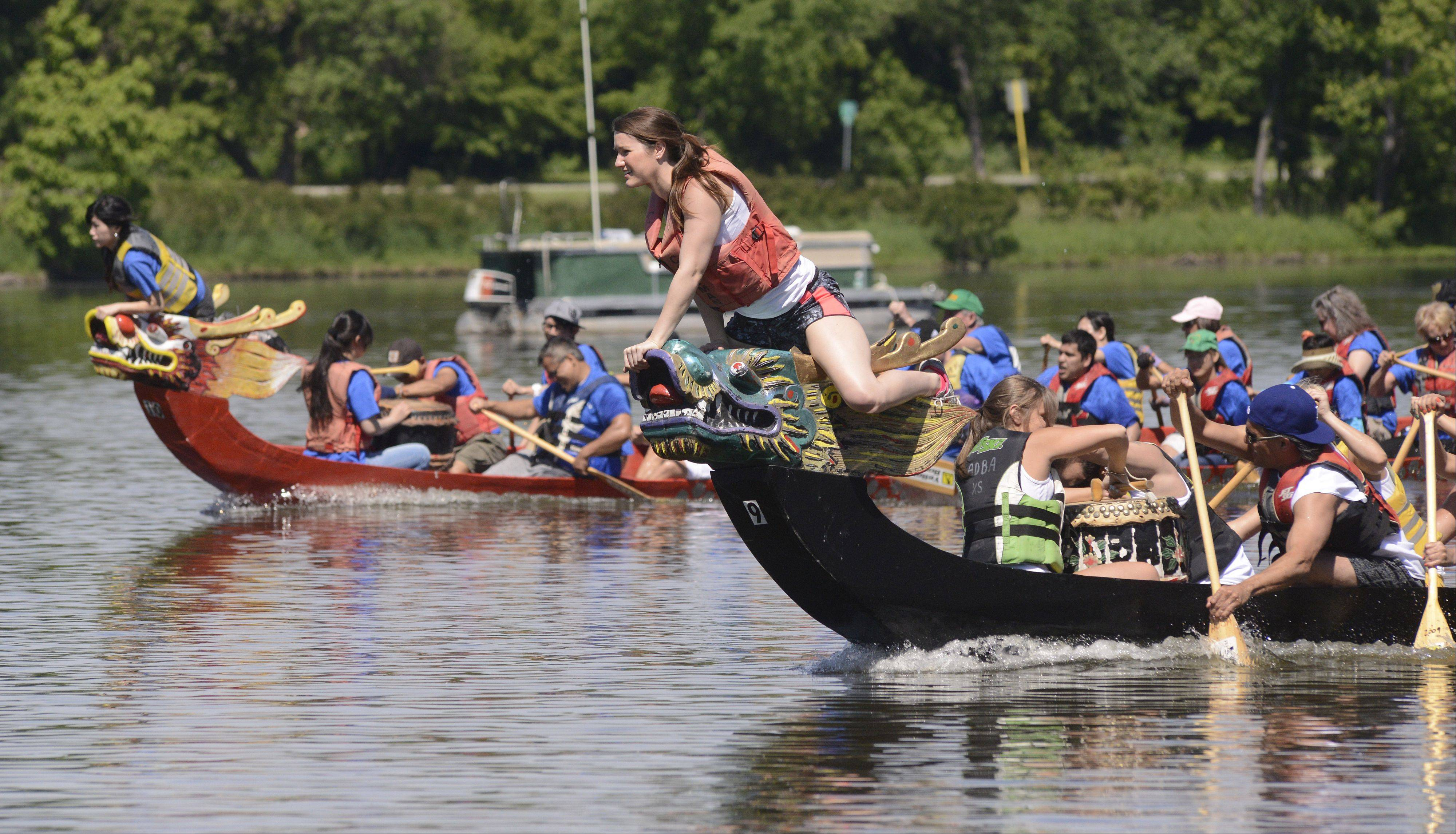 Ally Ferrandino of the Rookies Bar and Grill dragon boat team is ready to grab the flag for the win while racing Elgin Community College's team in the time trials at the St. Charles RiverFest on Saturday.