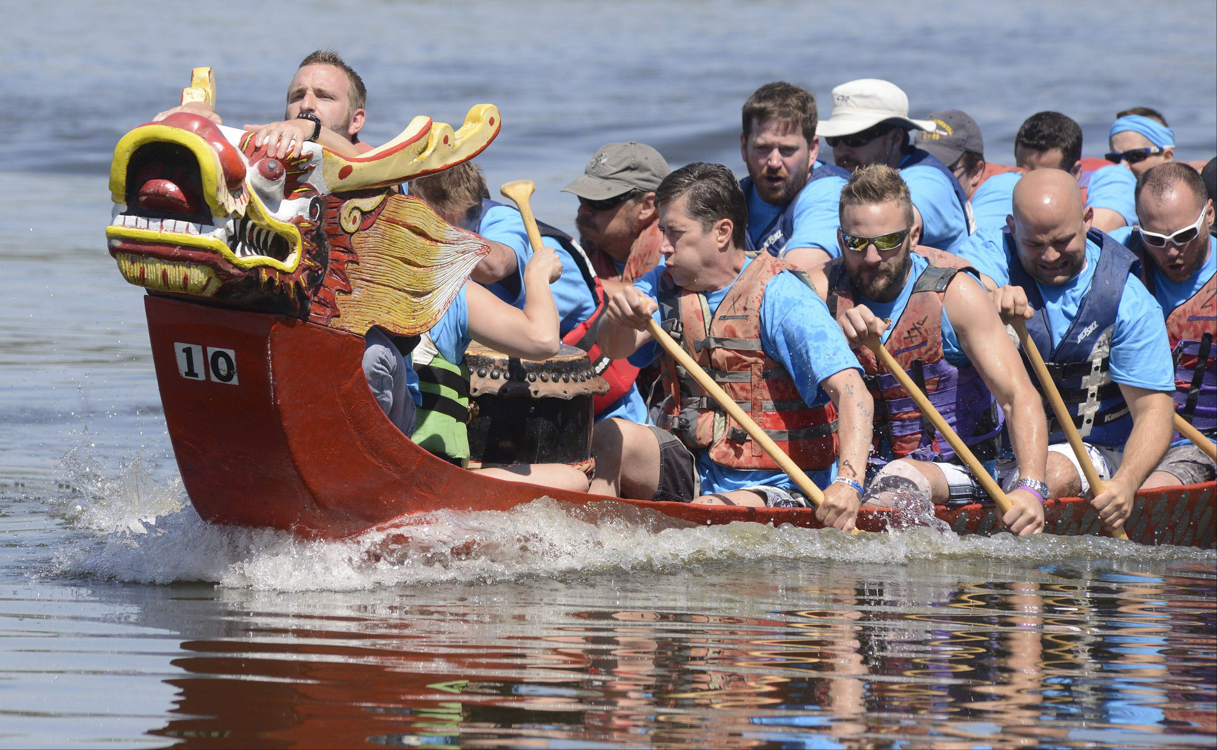 "Jonny Walker of St. Charles waits for the moment to climb atop the dragon head to grab the flag for the win during the annual dragon boat races at St. Charles RiverFest on Saturday. Walker and teammates ""Jump Ship"" are all from the St. Charles and Geneva area."