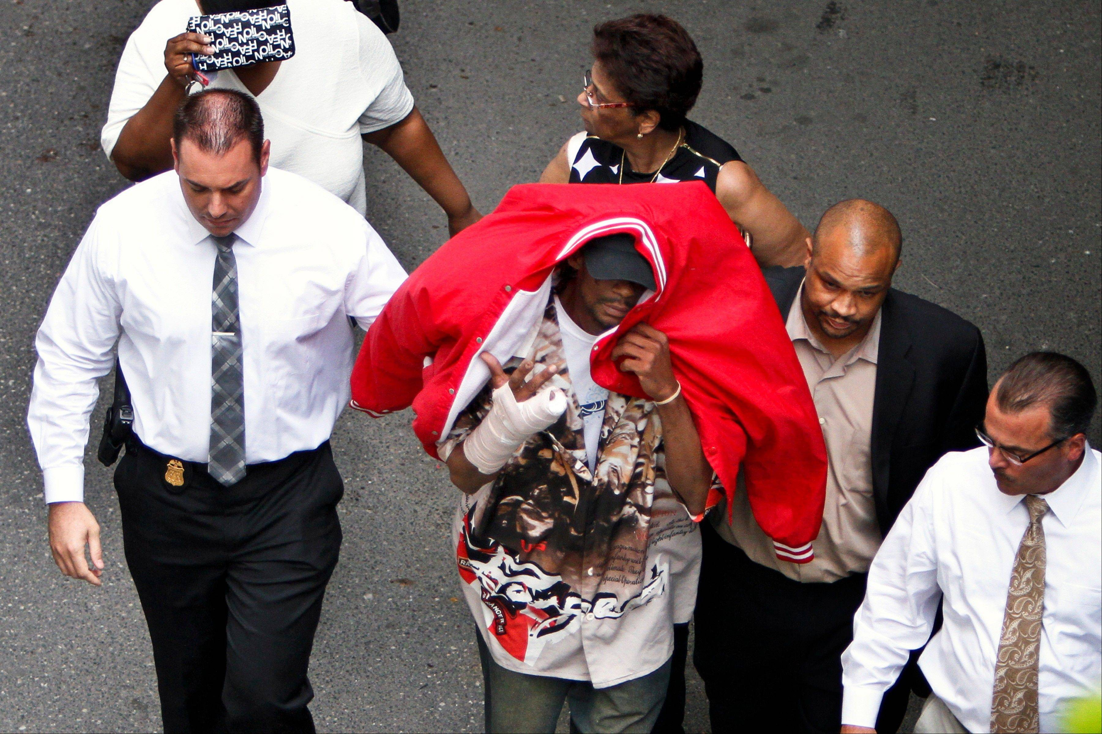 Sean Benschop, center, with red jacket over his head, walks Saturday with investigators as he arrives at the Philadelphia Police Department's Central Detectives Division in Center City Philadelphia.