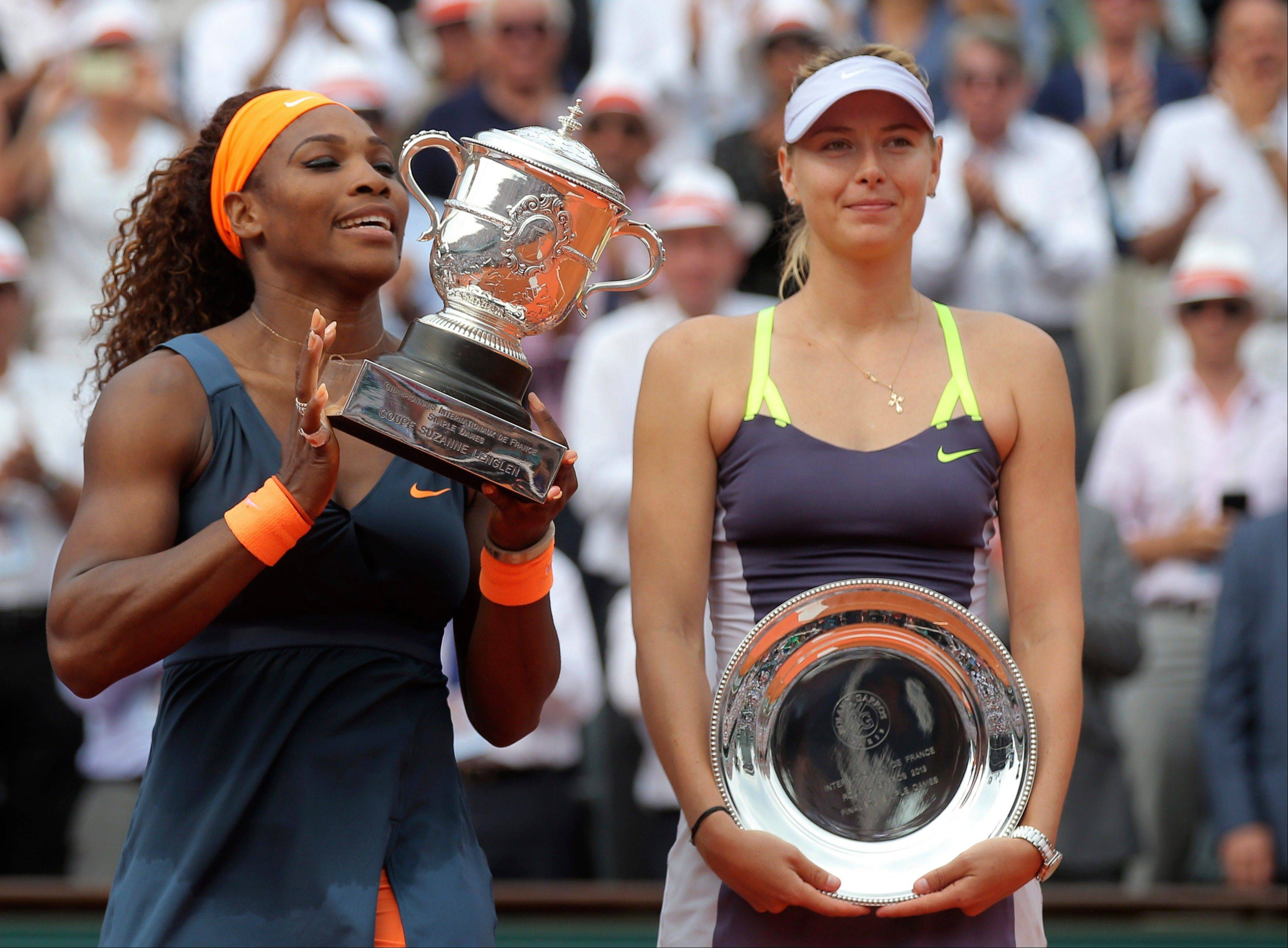 Serena Williams, of the U.S., left, holds the winner's cup after defeating Russia's Maria Sharapova after the Women's final match of the French Open tennis tournament at the Roland Garros stadium Saturday, June 8, in Paris. Williams won 6-4, 6-4.