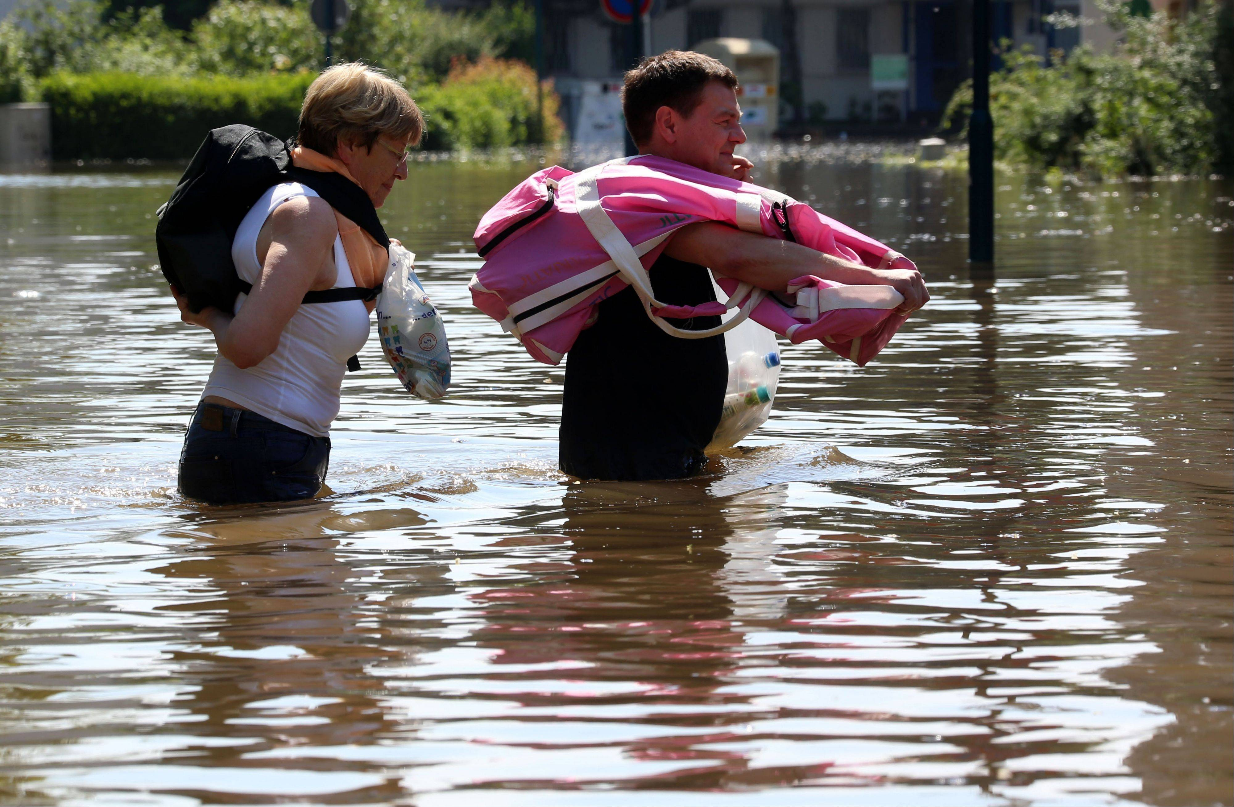 Inhabitants carry belongings through the floods of river Elbe in Magdeburg, eastern Germany, Saturday June 8. German news agency dpa said people in Magdeburg in Saxony-Anhalt were anxiously awaiting the crest of the Elbe river on Saturday, while residents further upstream were starting to clean up the debris that was left along the river. In Magdeburg, authorities evacuated a nursing home and turned off electricity in several parts of the city. High water levels were also reported from Hungary, Slovakia and the Czech Republic, while thousands of people in Austria were busy shoveling away the mud left by the receding floodwaters of the Danube.
