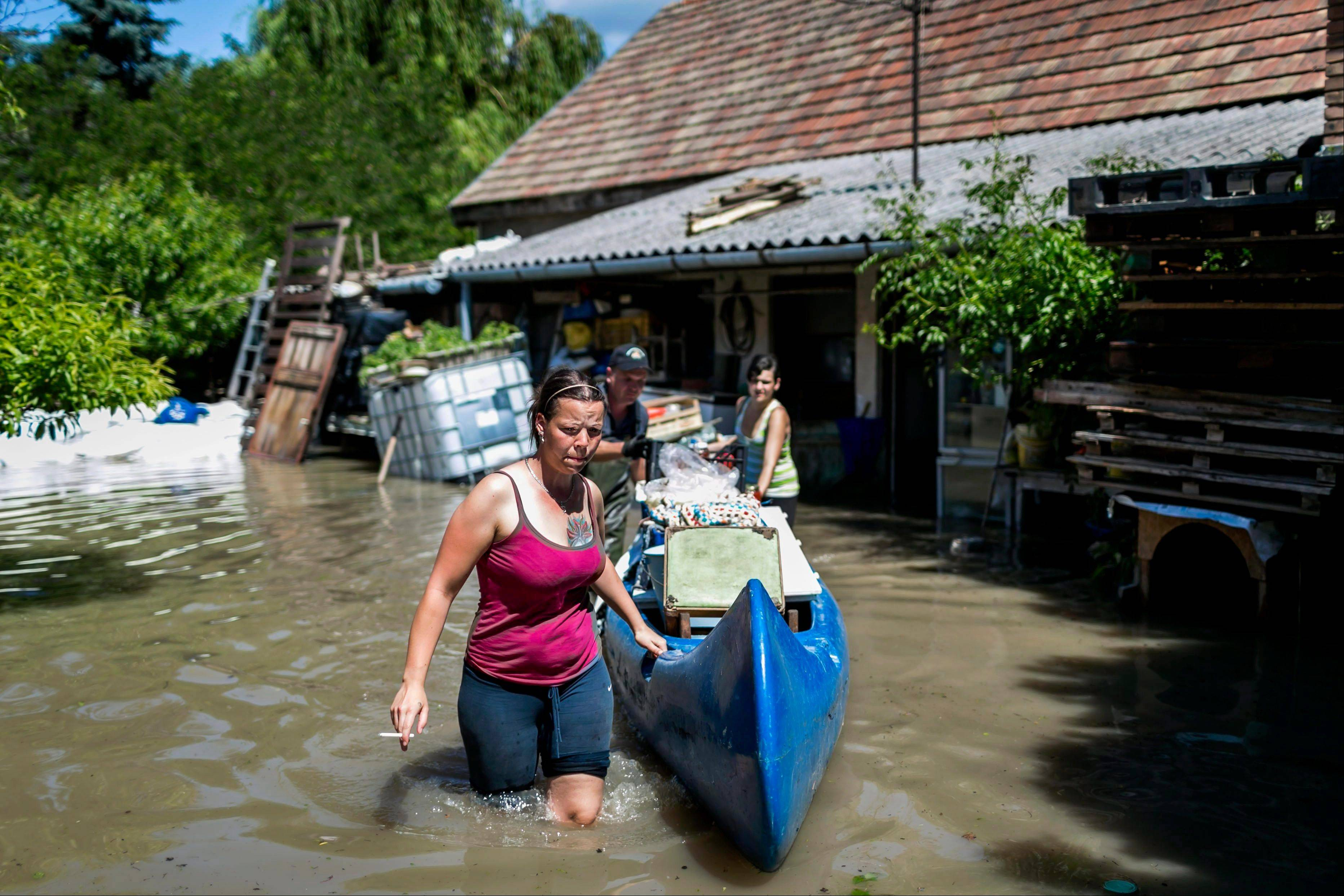 Women and an emergency worker, rear, use a canoe to empty a home flooded by River Danube in Dunabogdany, 22.3 miles north of Budapest, Hungary, Saturday, June 8. Heavy rainfalls in the past days cause flooding along rivers and lakes in Germany, Austria, Switzerland the Czech Republic and Hungary.