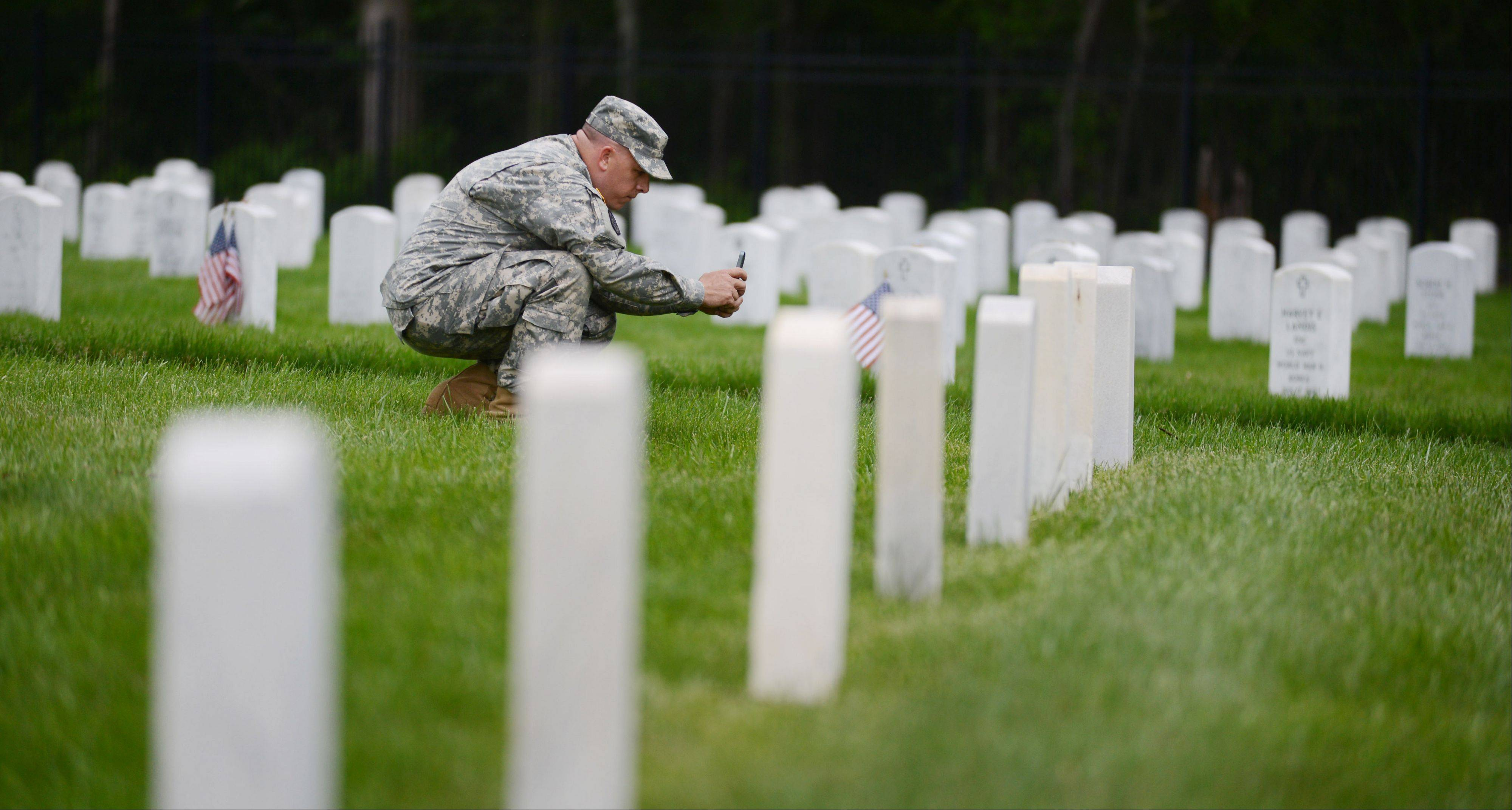 U.S. Army Sgt. John Roloson of Fort McCoy in Wisconsin uses an iPhone to photograph a grave marker at the Fort Sheridan Cemetery. The project is an effort to produce an online, searchable database and a smartphone app to allow visitors to find grave locations and view photos.