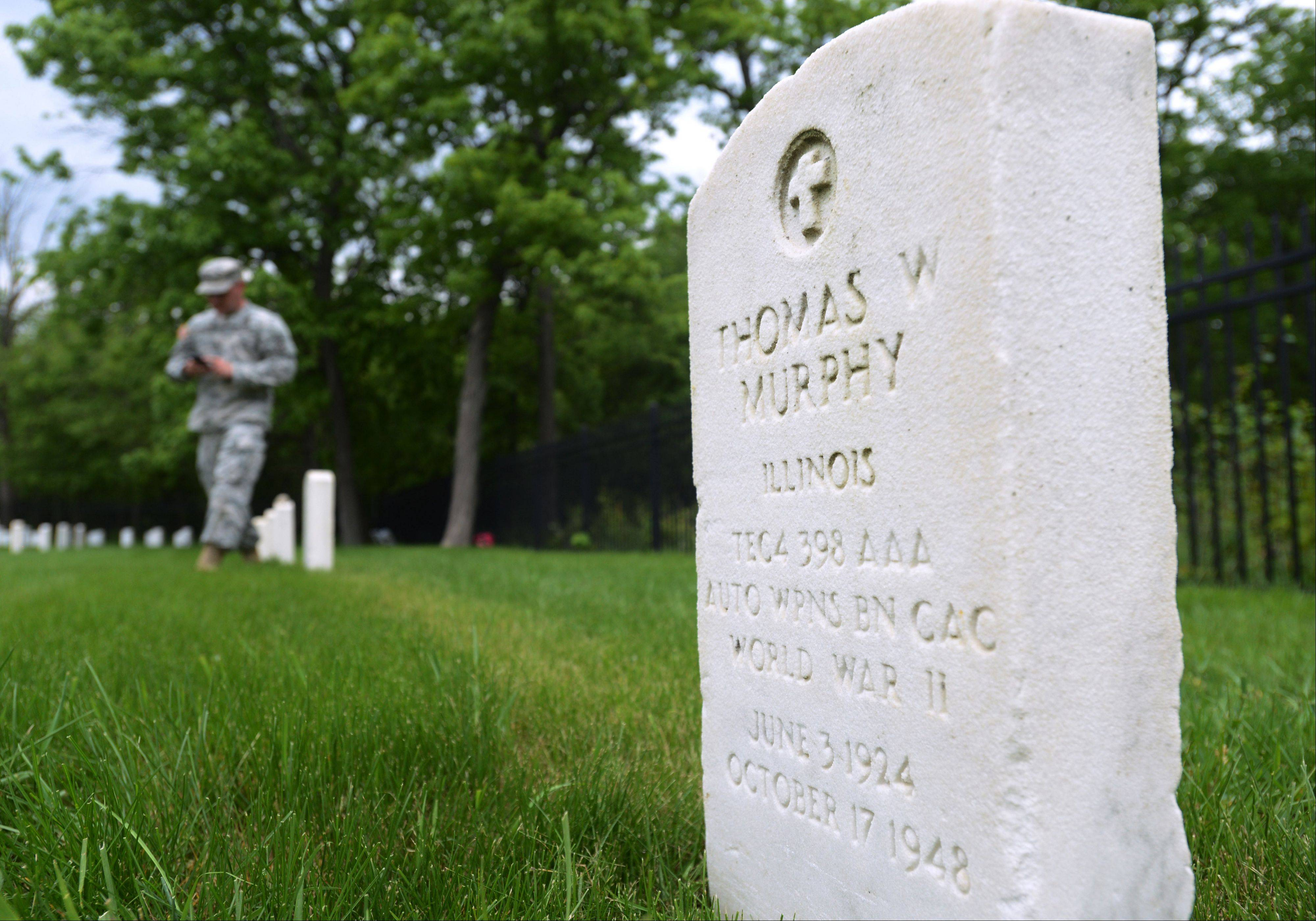 Sgt. 1st Class Larry Parks photographs grave markers at the Fort Sheridan Cemetery near Highland Park.