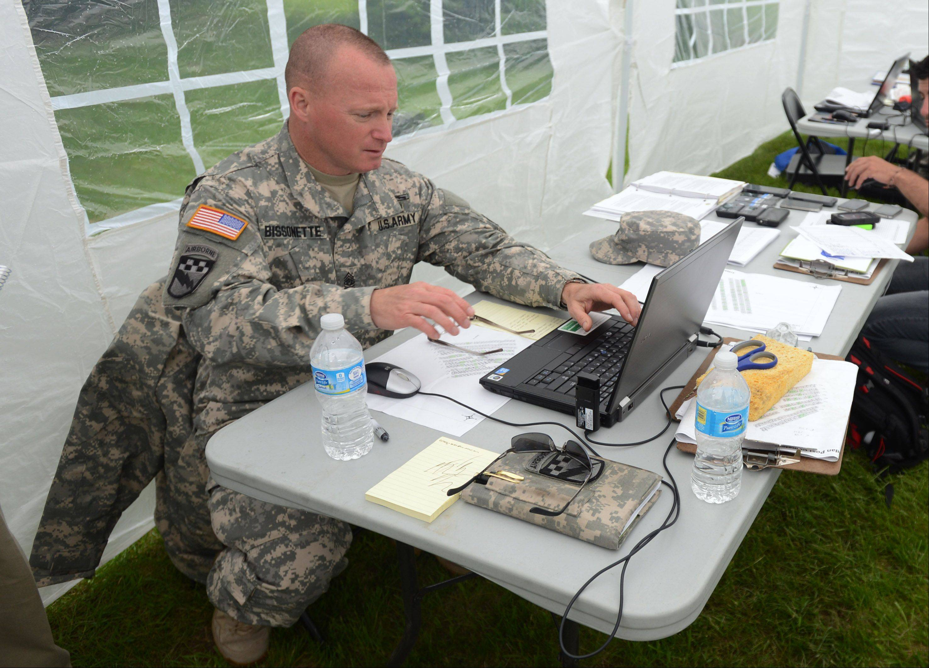 Sgt. Maj. Bill Bissonette from Fort McCoy in Wisconsin works in a tent where information is gathered and processed at the Fort Sheridan Cemetery.