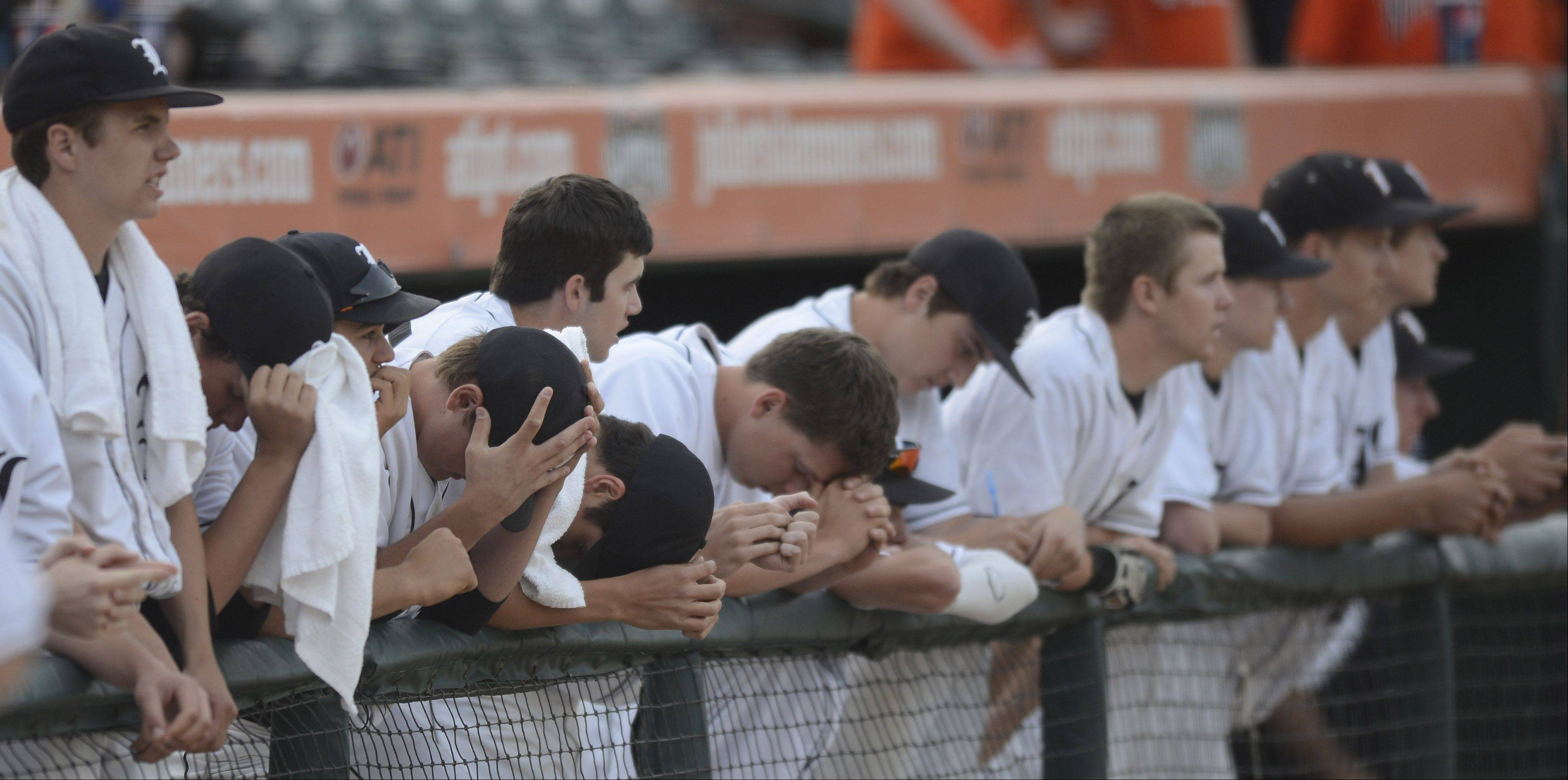 Libertyville players stand together in their dugout as fireworks are launched in celebration of Mt. Carmel's victory in the Class 4A state baseball championship game at Silver Cross Field in Joliet Saturday.