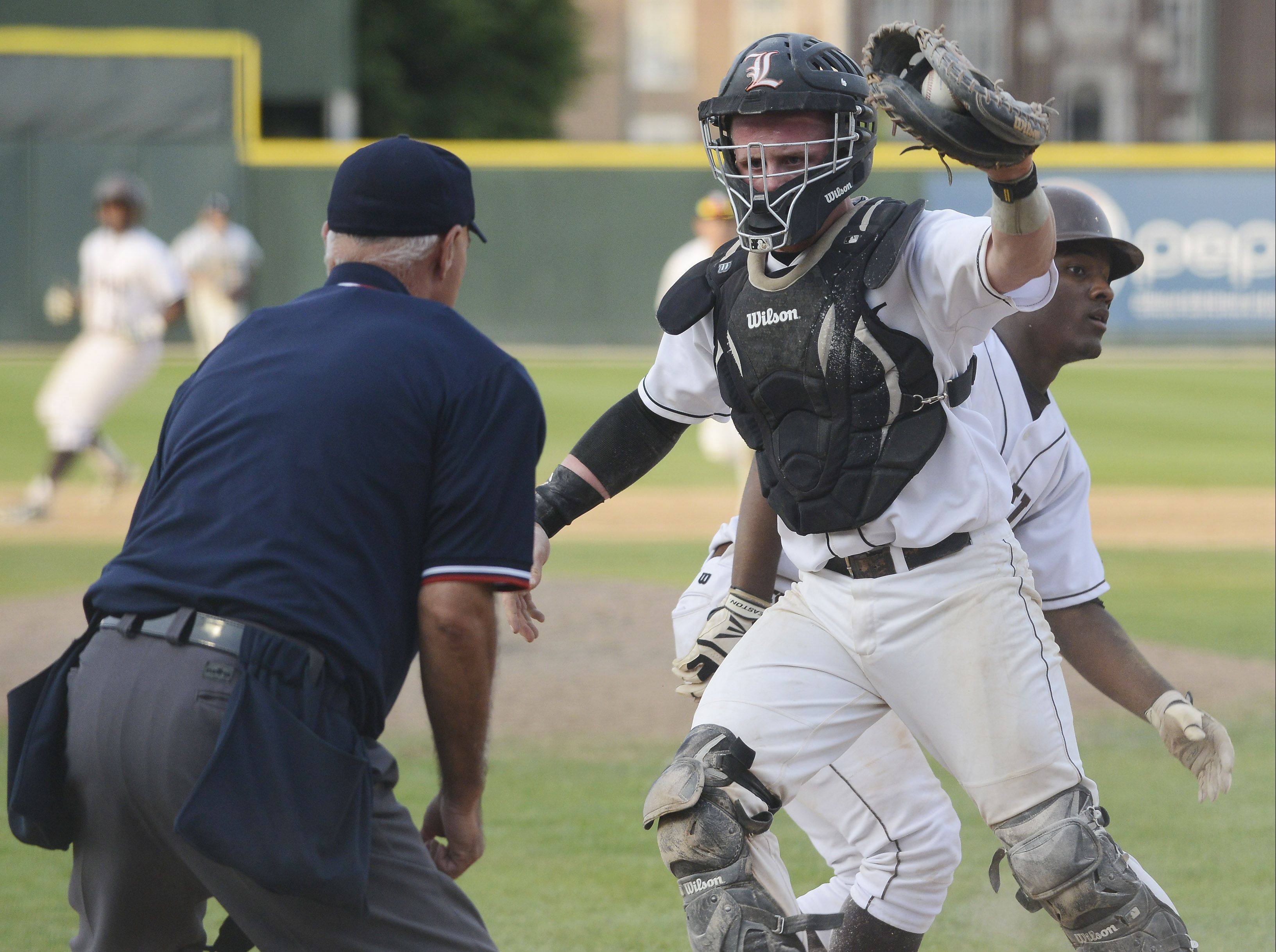 Libertyville catcher Evan Skoug holds up the ball for the umpire after tagging out Mt. Carmel's Joshua Stowers on an attempted steal of home in the seventh inning.