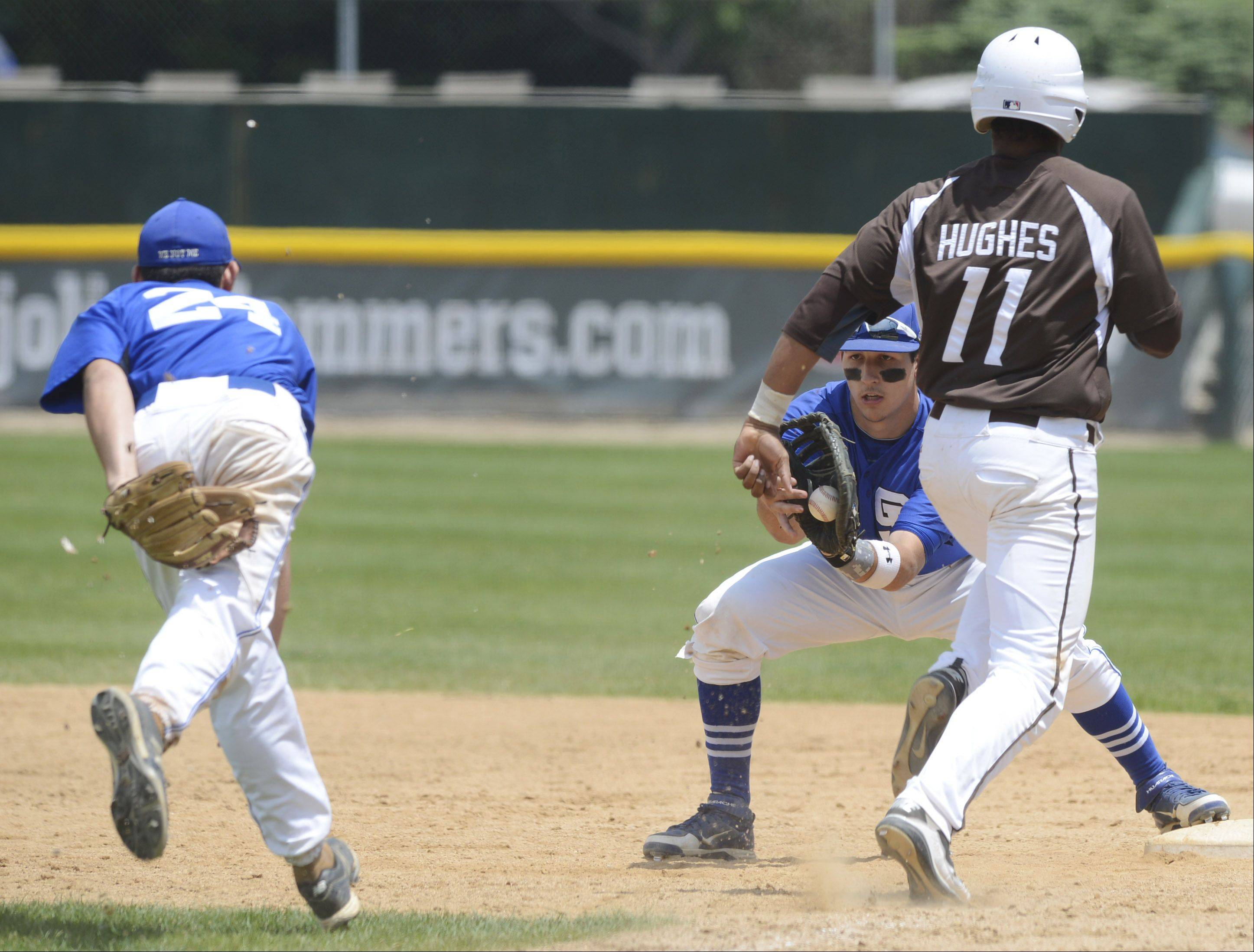 St. Francis first baseman Josh Croci catches a throw from pitcher Jason Sullivan in time to nab Joliet Catholic's Ira Hughes at first on a sixth-inning sacrifice during the Class 3A state baseball championship game at Silver Cross Field in Joliet on Saturday.