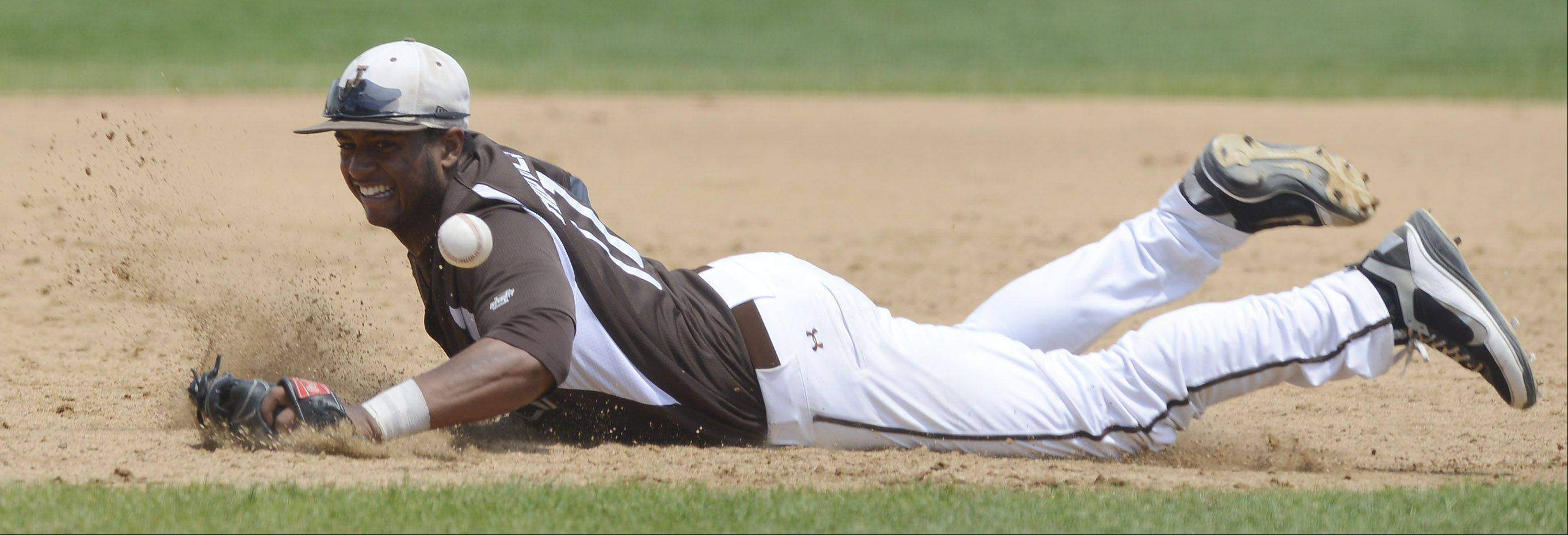Joliet Catholic third baseman Ira Hughes dives for a ground ball that went for a St. Francis hit during the Class 3A state baseball championship game at Silver Cross Field in Joliet Saturday.