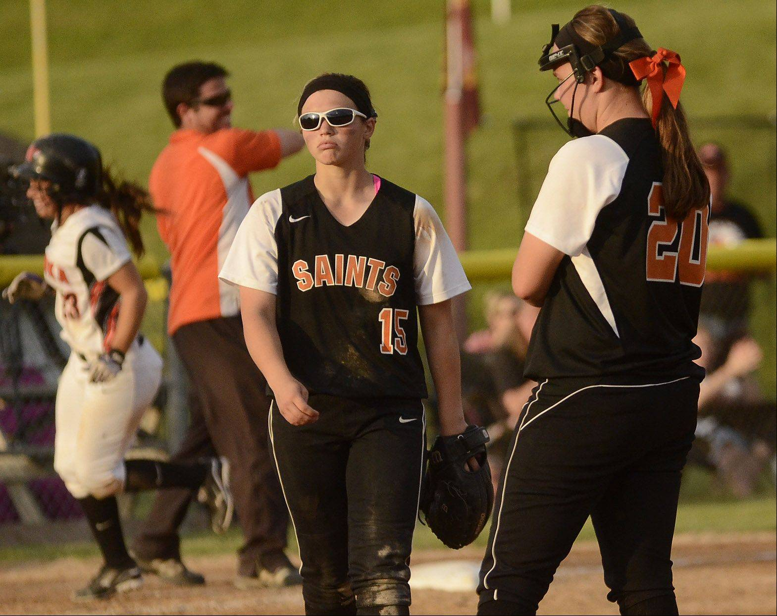 St. Charles East third baseman Alex Latoria and pitcher Haley Beno watch dejectedly as Minooka's Jordyn Larsen rounds the bases during her 5th inning home run as Minooka routs St. Charles East 14-3 in the Class 4A softball championship game.