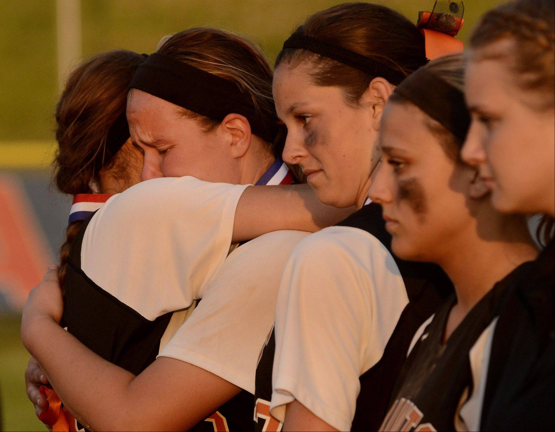 St. Charles East pitcher Haley Beno, center, is consoled by teammates after losing the Class 4A softball championship to Minooka.