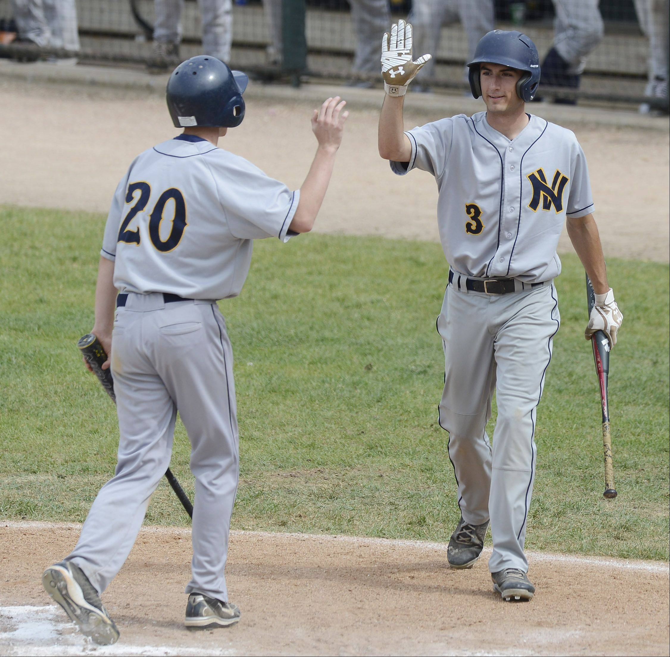 Neuqua Valley's Matt Butler gets a high-five from teammate Josh Piotrowski during the second inning of the Class 4A baseball third-place game at Silver Cross Field in Joliet on Saturday.