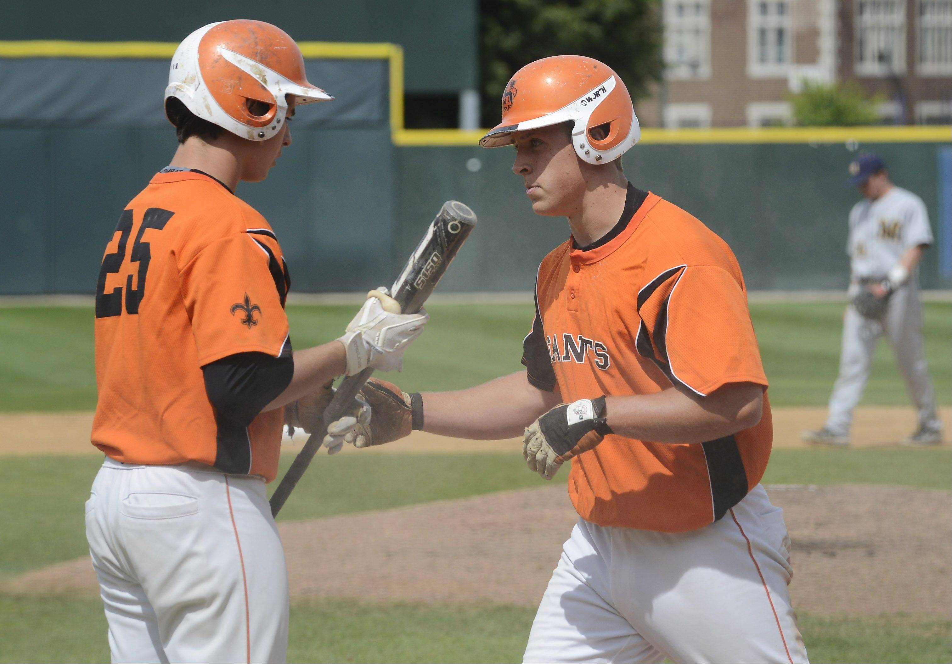 St. Charles East's Joe Hoscheit, right, gets a fist bump from teammate Brian Sobieski after scoring against Neuqua Valley during the Class 4A baseball third-place game at Silver Cross Field in Joliet on Saturday.