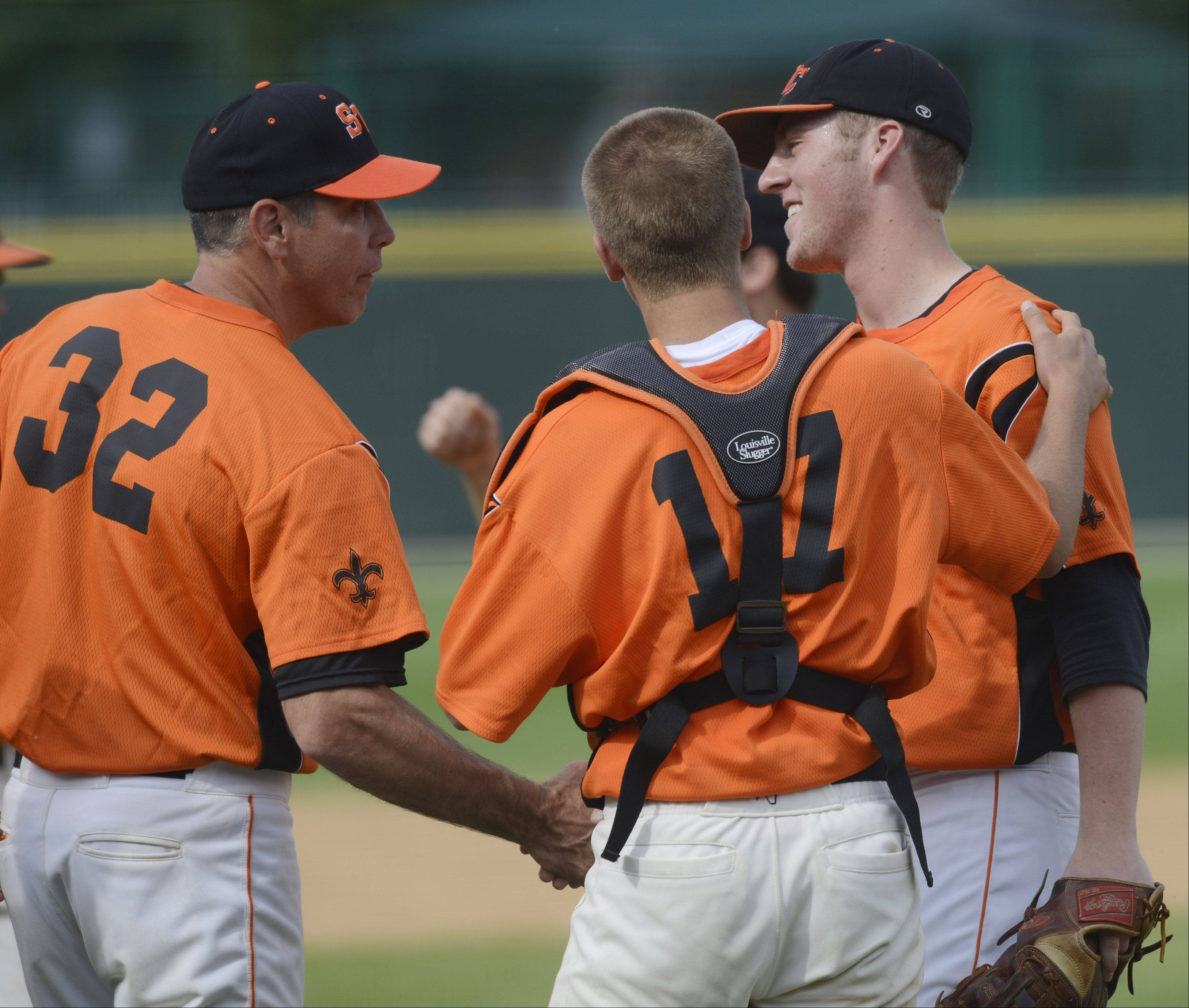 St. Charles East pitcher Troy Dyhkuis, right, is congratulated after following his 2 innings of relief in the Class 4A baseball third-place game at Silver Cross Field in Joliet on Saturday.