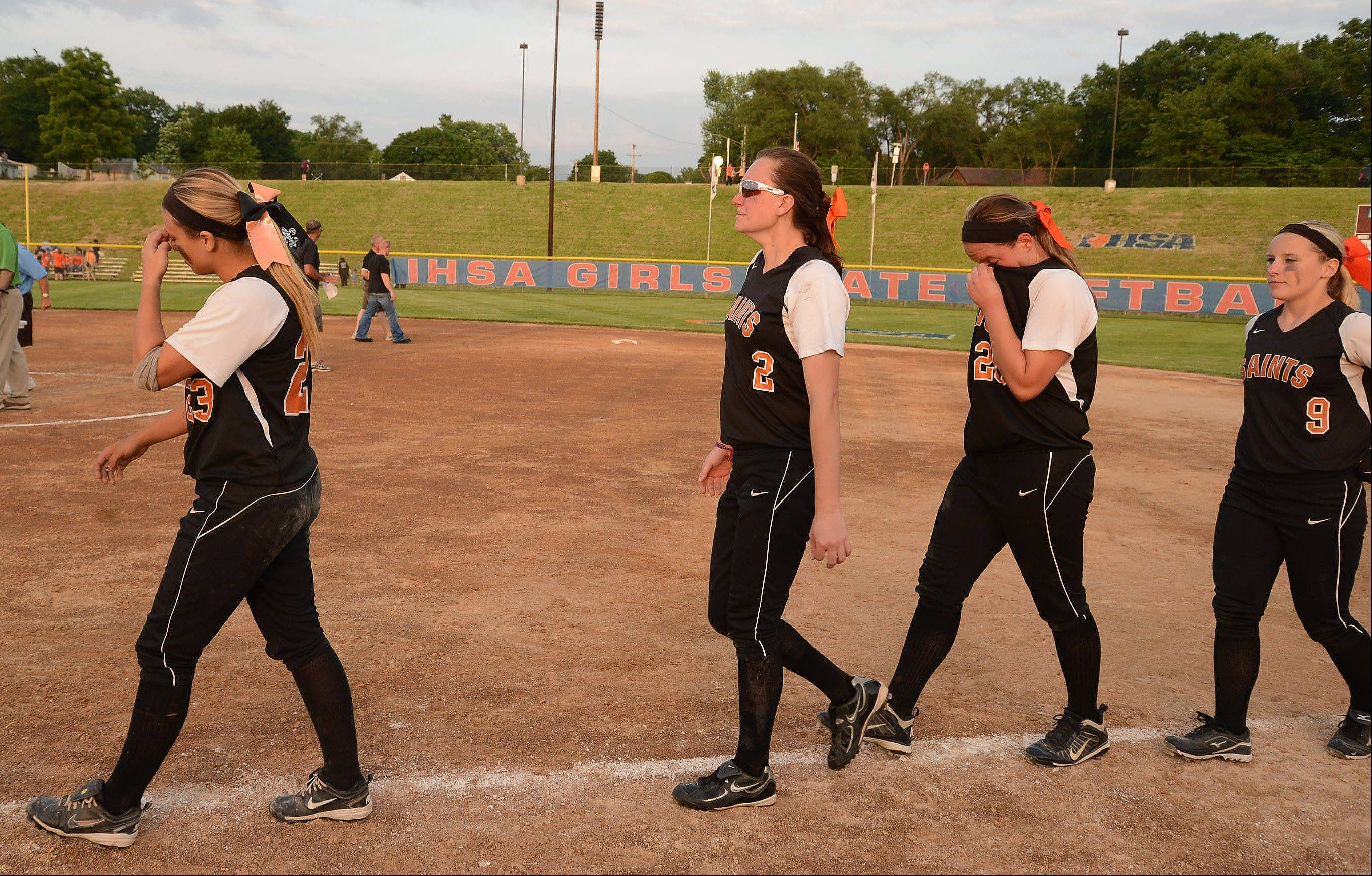 St.Charles East players walk off the field dejectedly after losing to Minooka in the Class 4A softball championship game.