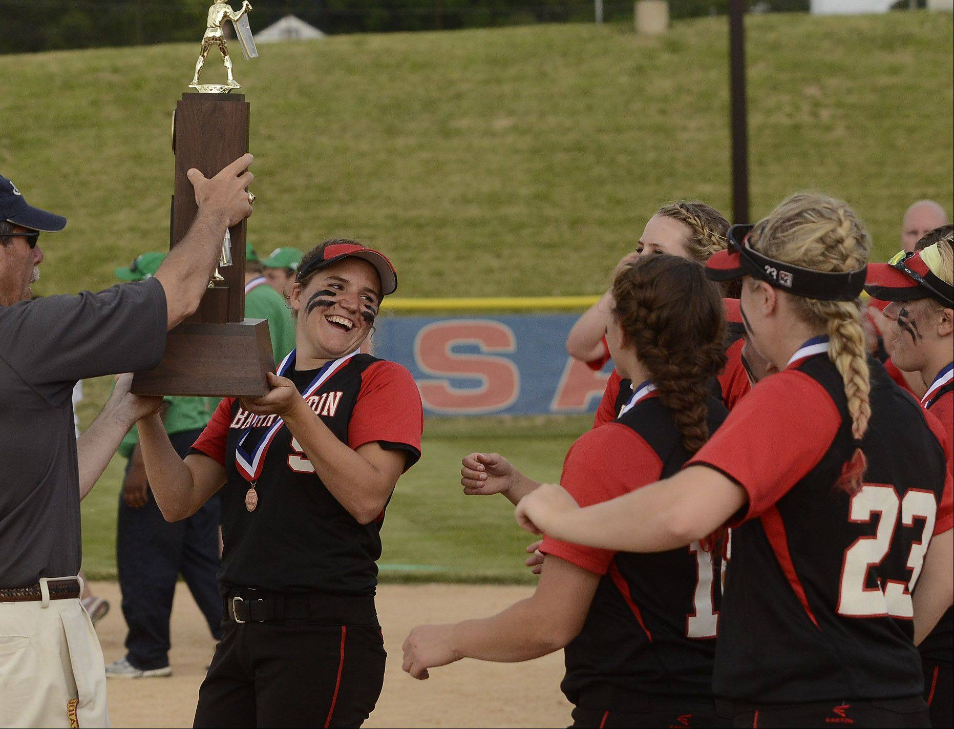Barrington's Maggie O'Hara hoists the Class 4A third place trophy after Barrington defeats York 5-1.