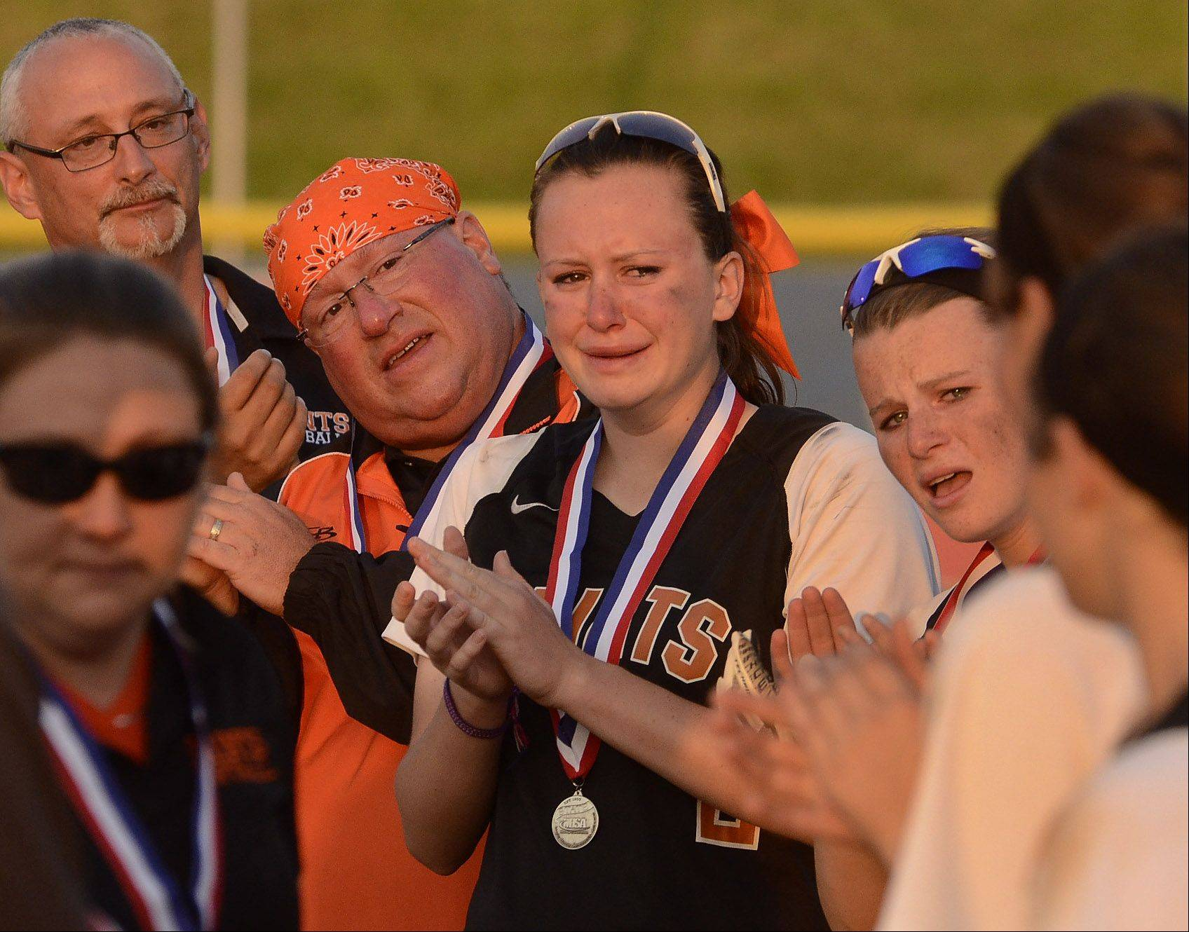 With tears in her eyes, Olivia Lorenzini applauds her teammates as they receive their 2nd place medals after losing the Class 4A softball championship game to Minooka.
