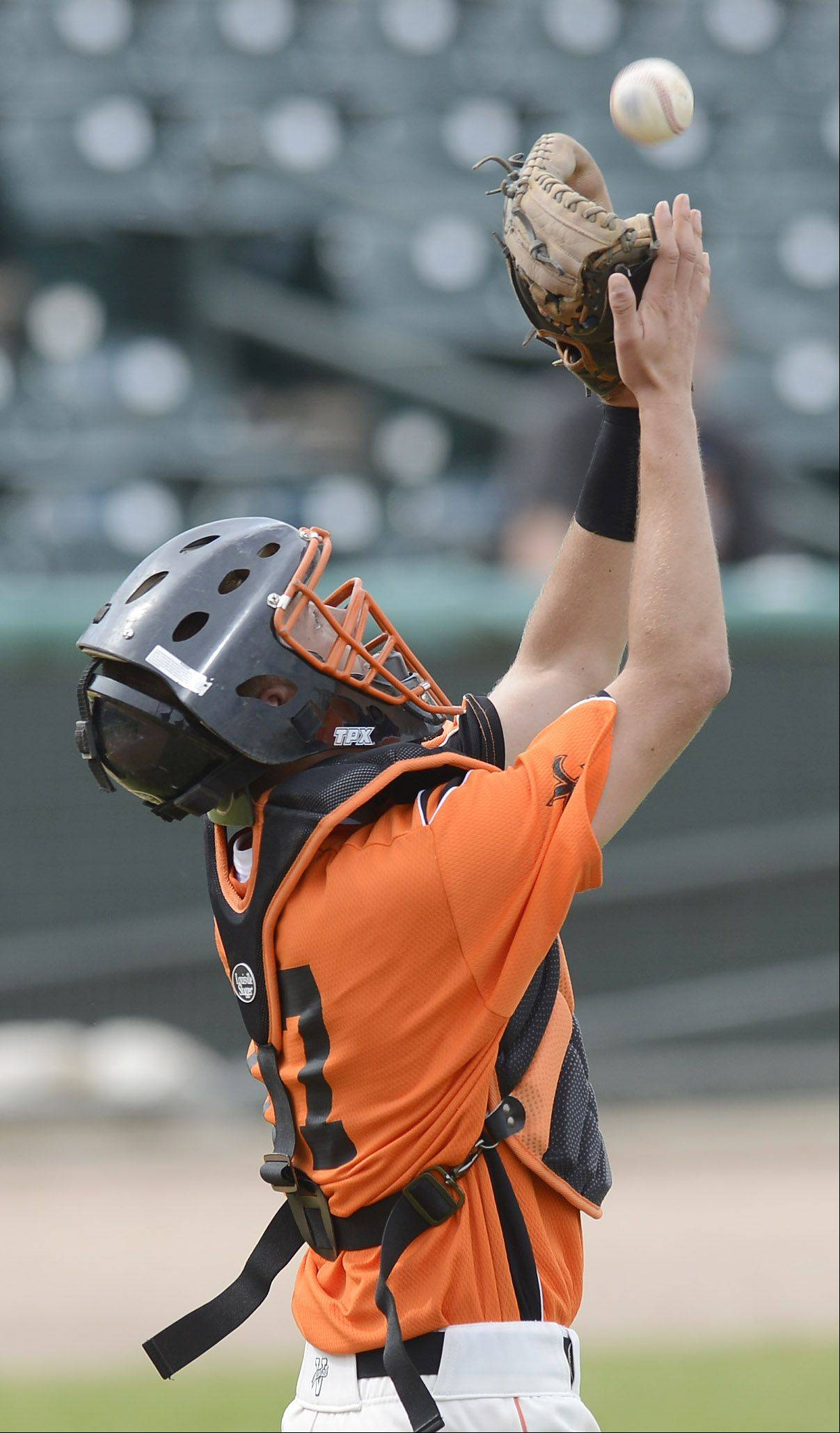 St. Charles East catcher Adam Rojas catches a pop fly on the infield during the Class 4A state baseball third-place game at Silver Cross Field in Joliet Saturday.