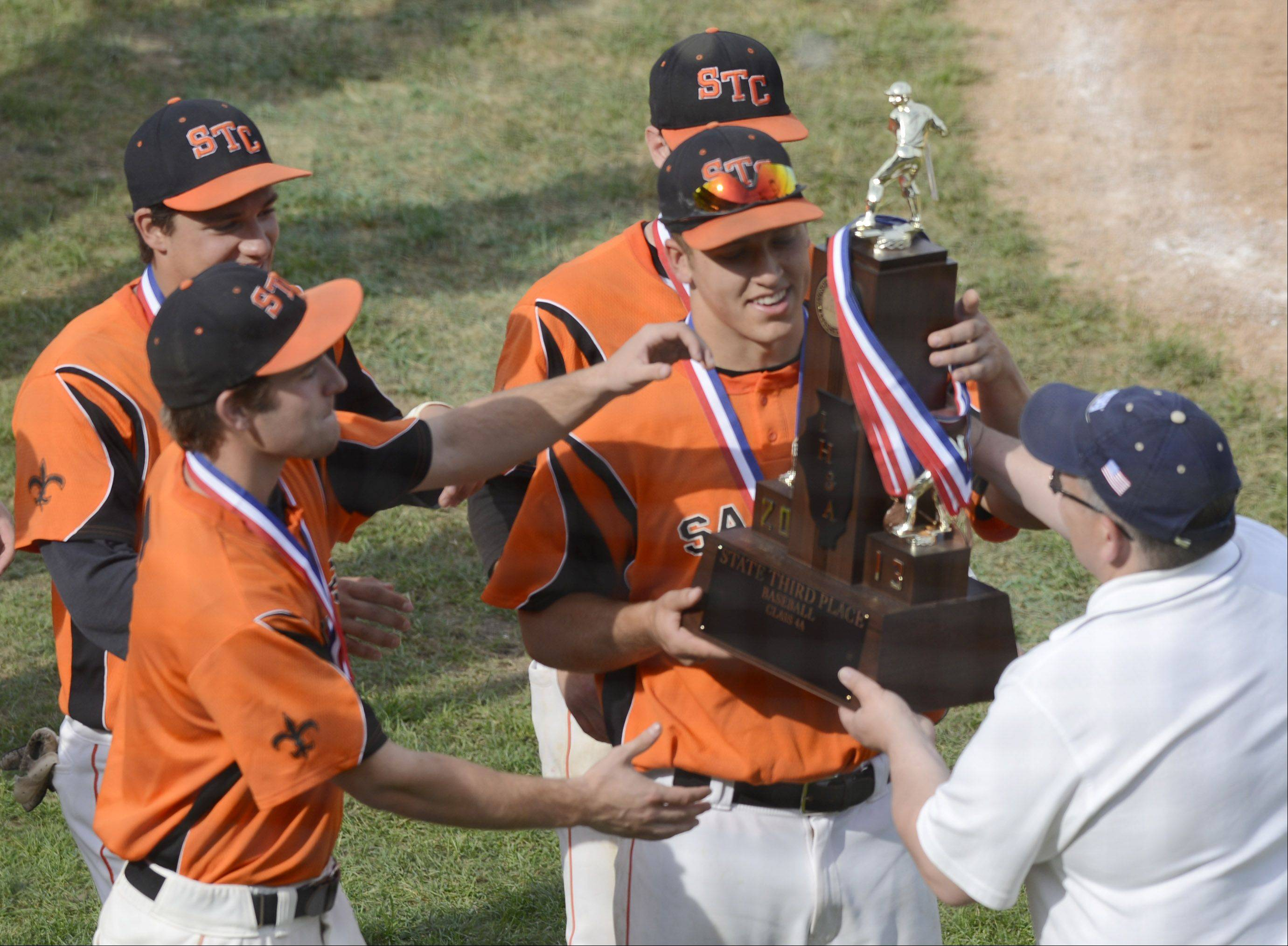 St. Charles East players receive their third-place trophy following the Class 4A state baseball third-place game against Neuqua Valley at Silver Cross Field in Joliet Saturday.