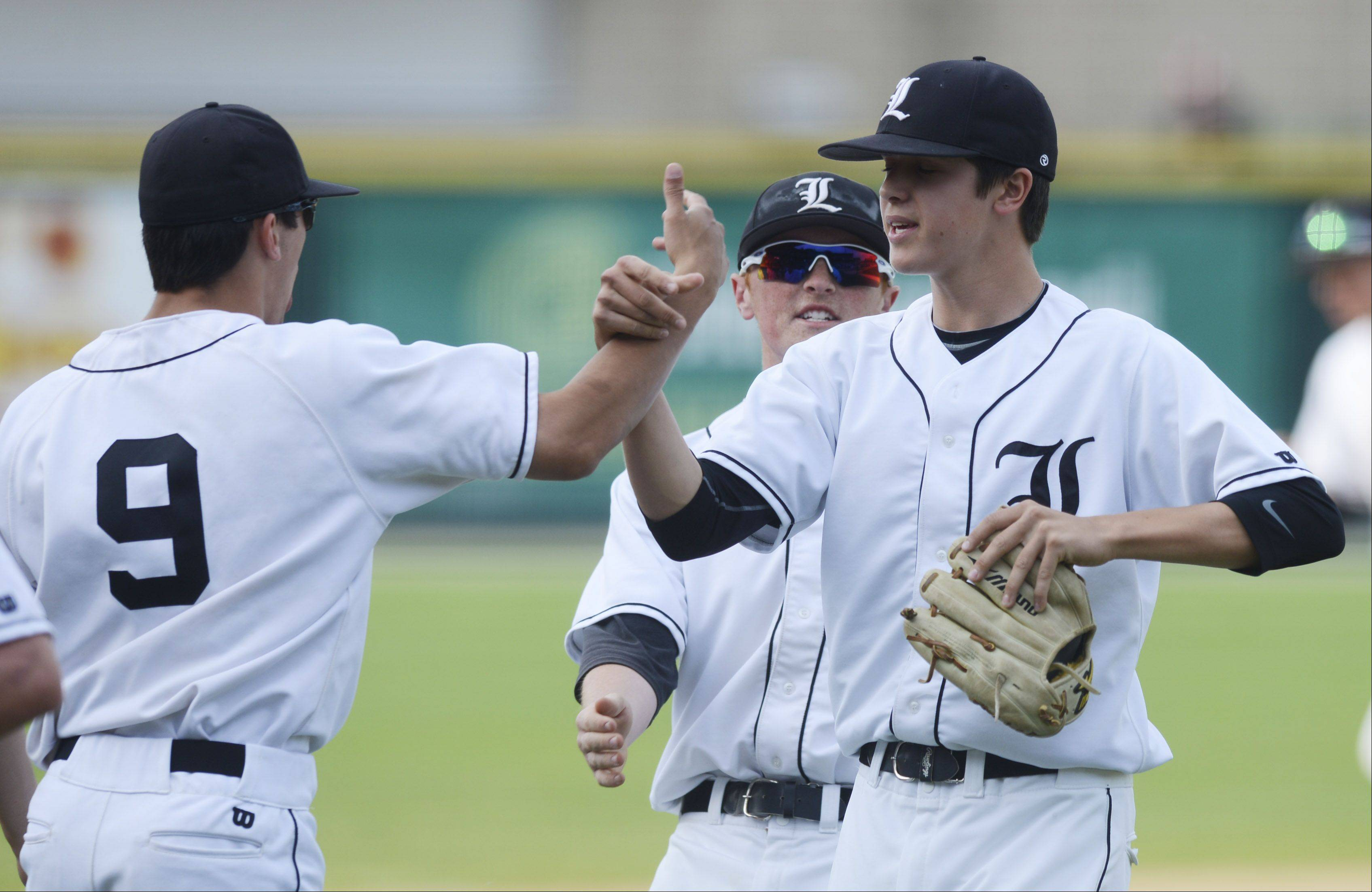 Libertyville pitcher Nate Cote gets a high five from teammate Dereck Loos after the first inning of the Class 4A state baseball championship game against Mt. Carmel at Silver Cross Field in Joliet Saturday.